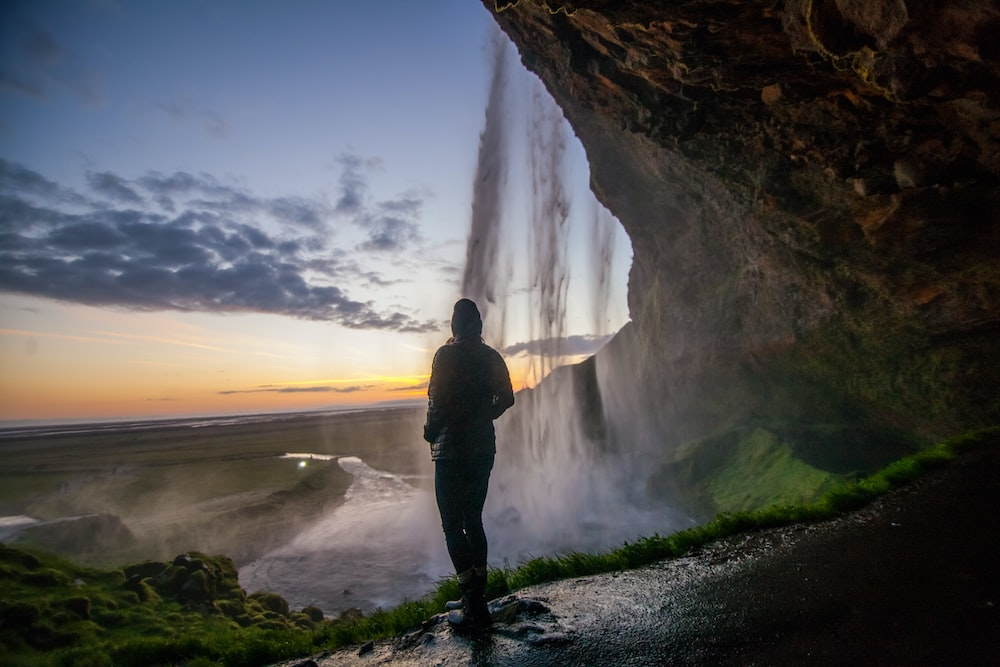 person standing under cave near waterfall