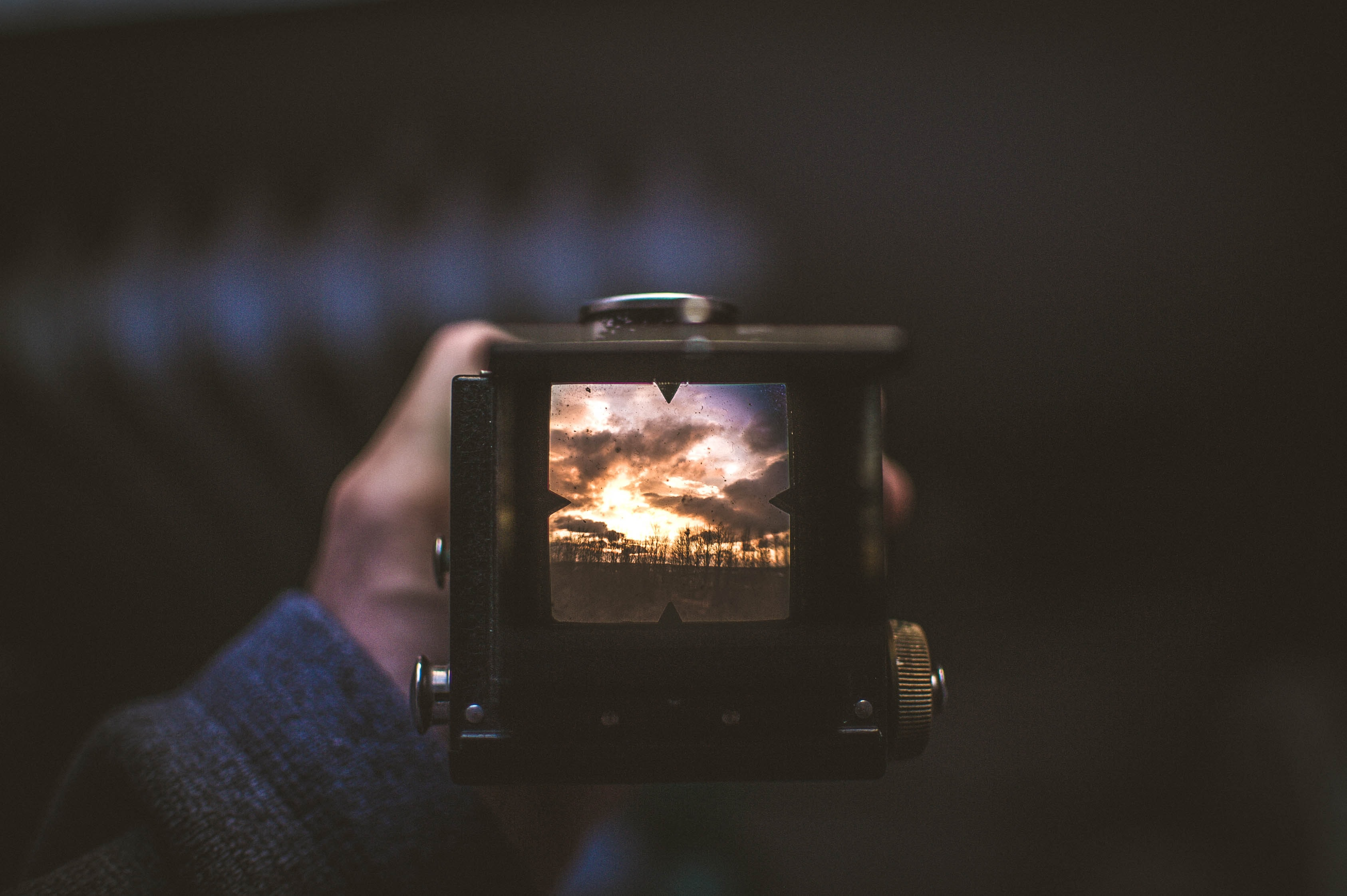 The viewfinder of a camera shows a photo of the sunset.