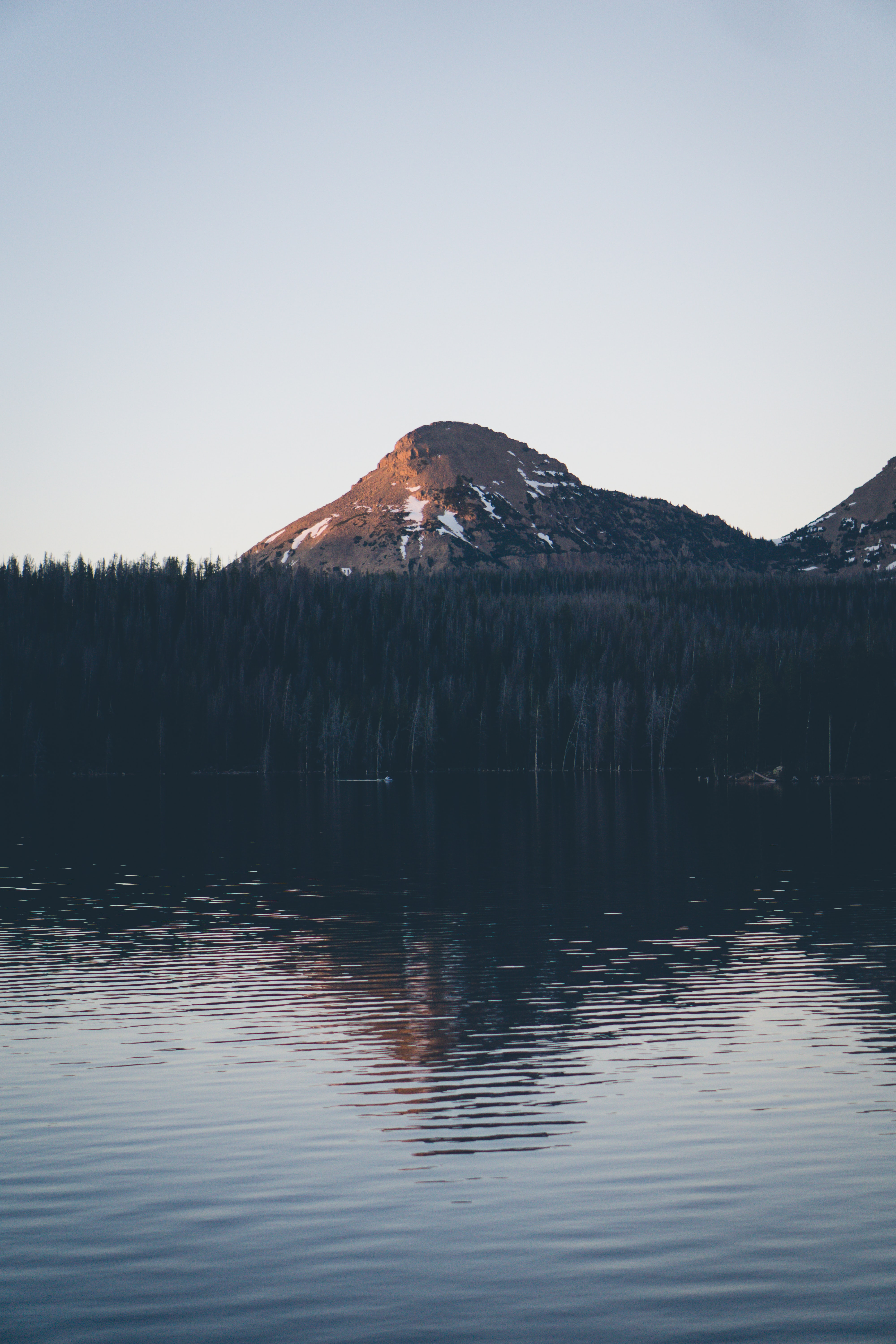 A mountain towering over a tree-lined lake