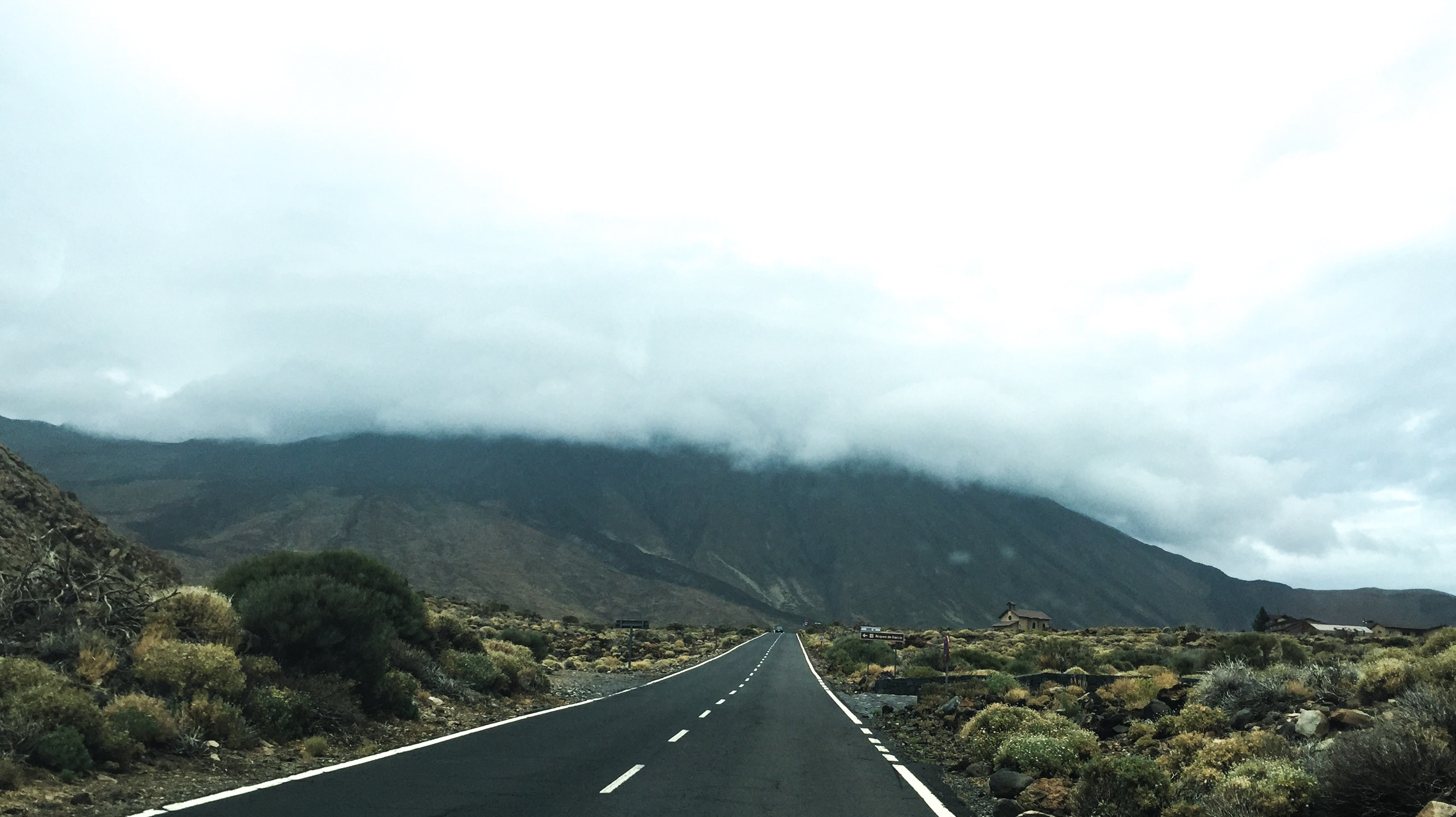 An empty road leading towards a mountain with mist rolling down its slopes