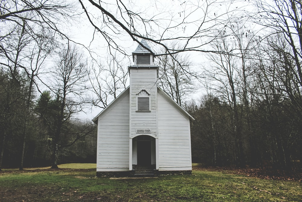 photo of white wooden chapel surrounded by trees during daytime