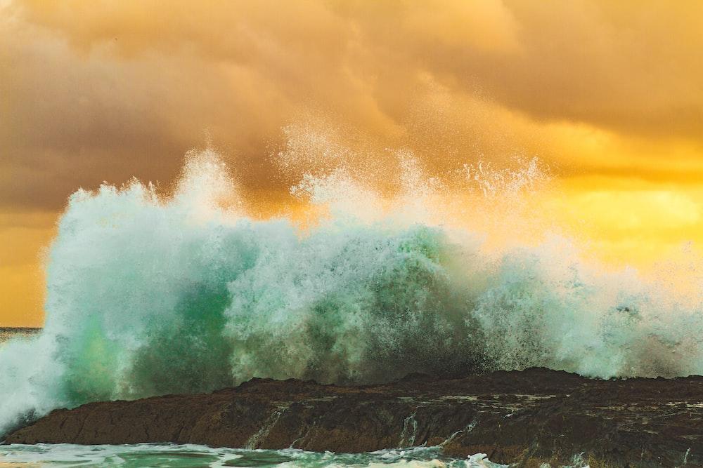 splash of body of water on rock