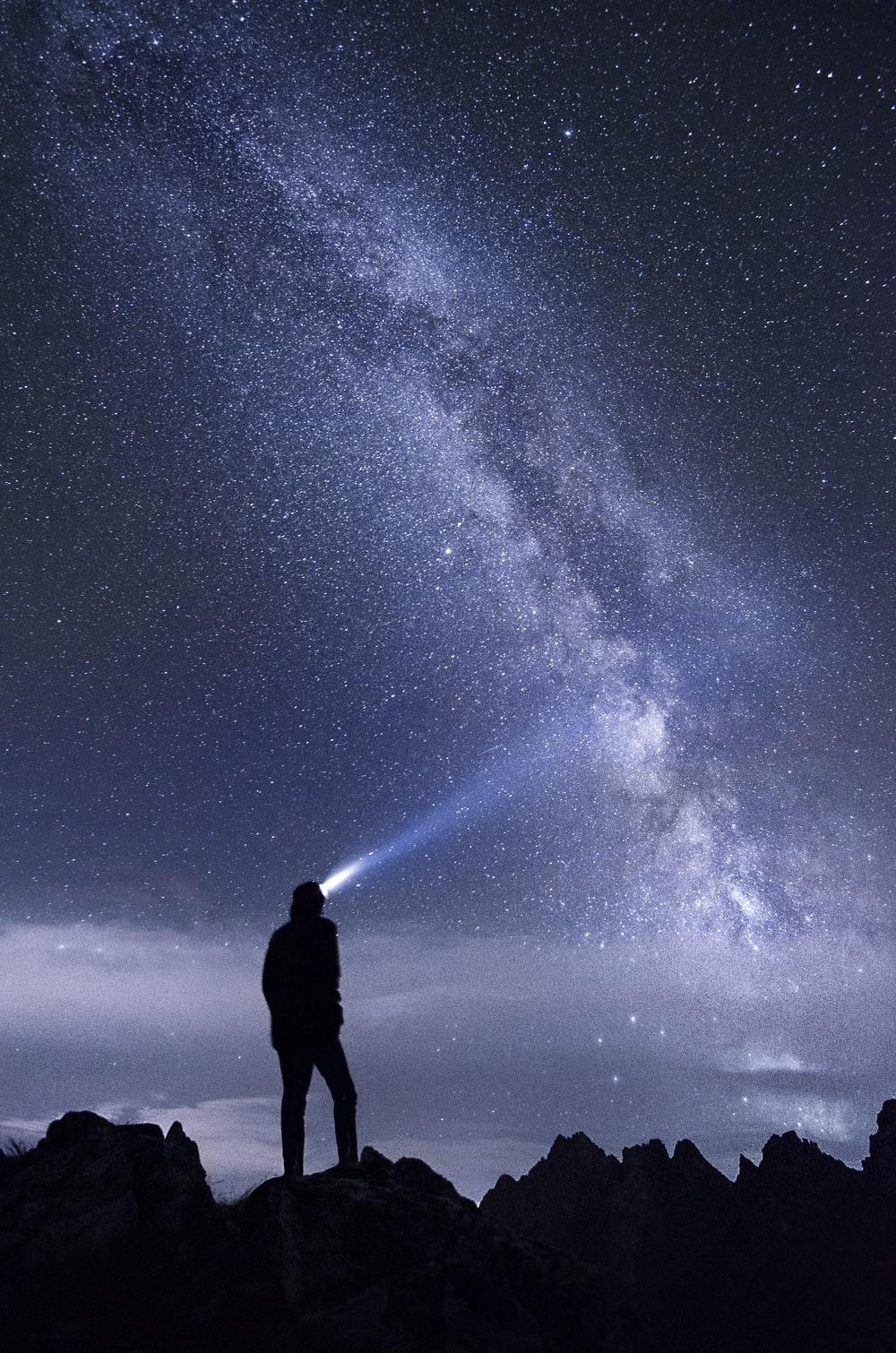 silhouette photo of man using headlamp standing on mountain