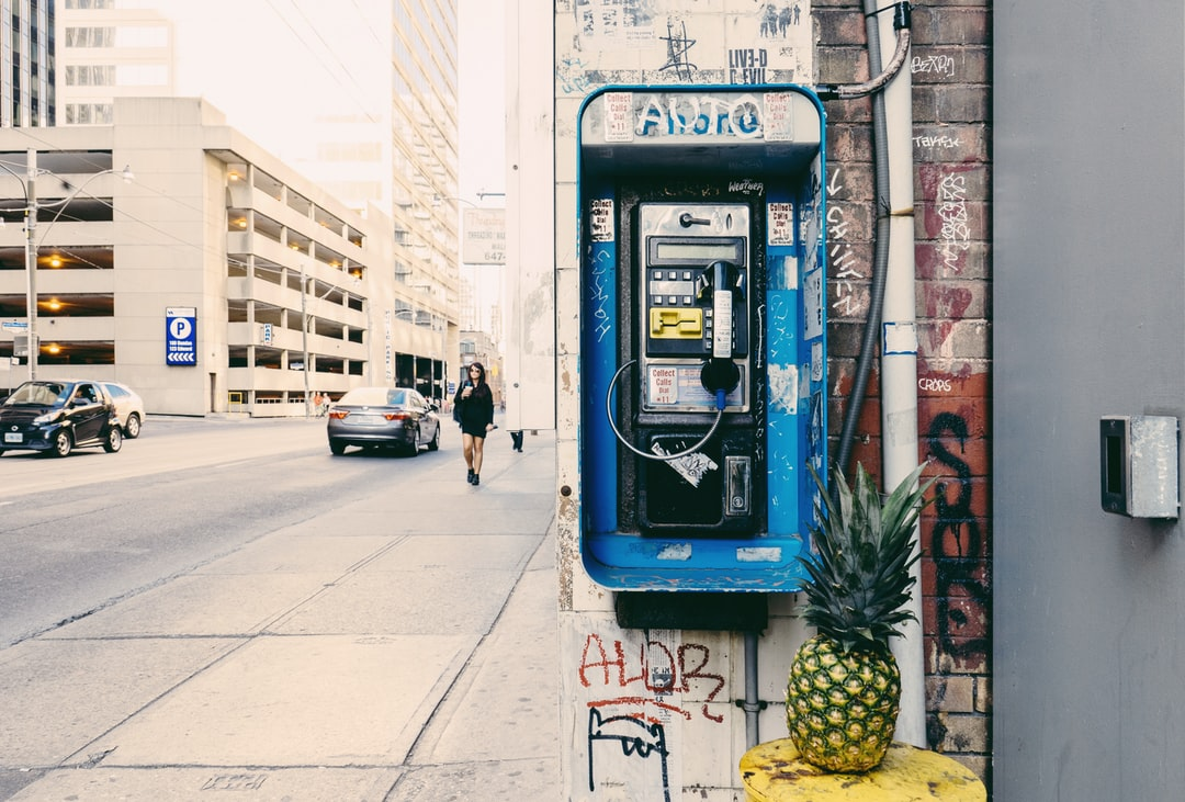 photo of a pineapple in front of a pay phone