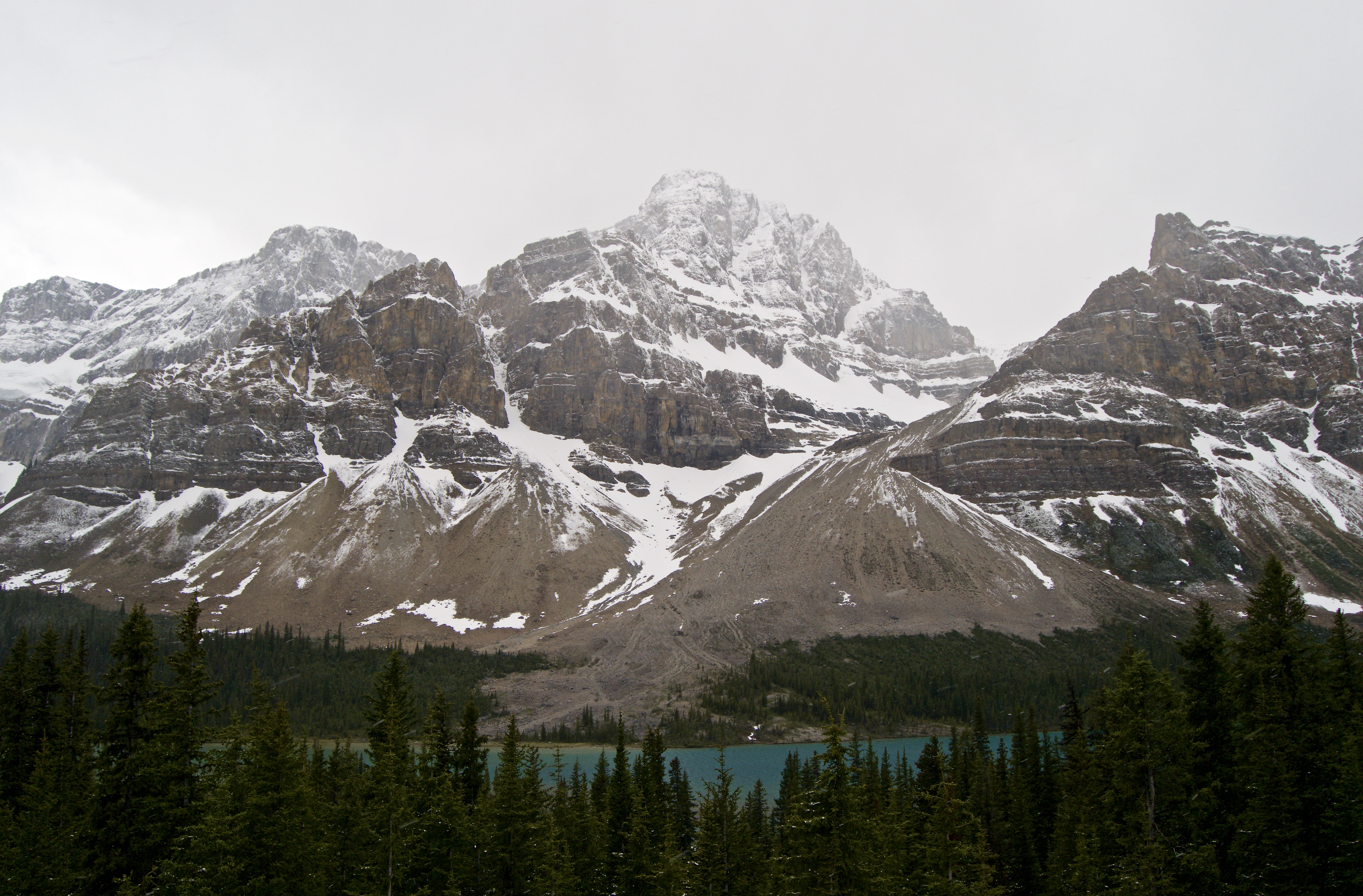 On a cloudy winter day in Canada, snow covers a rocky mountain range flanked with pine trees surrounding a lake