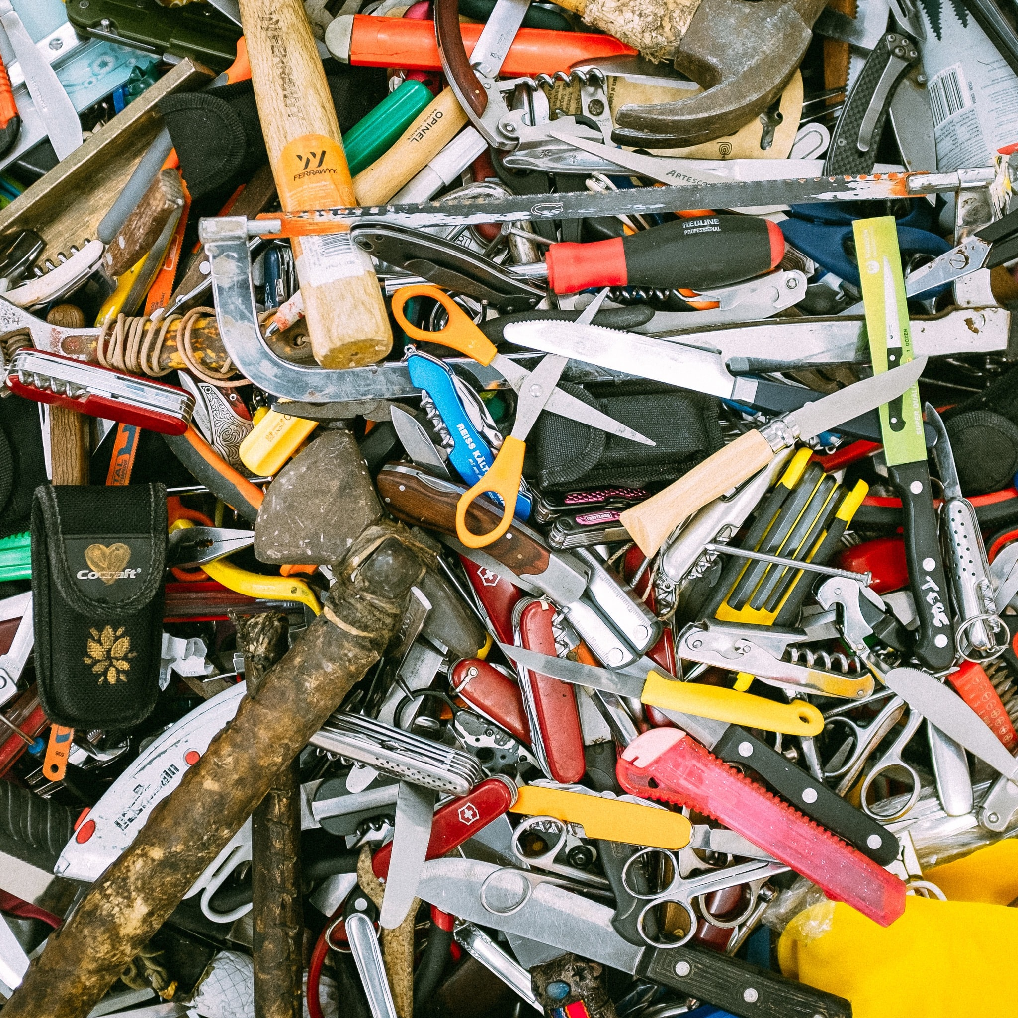 An overhead shot of a heap of scissors, knives, hammers and other tools