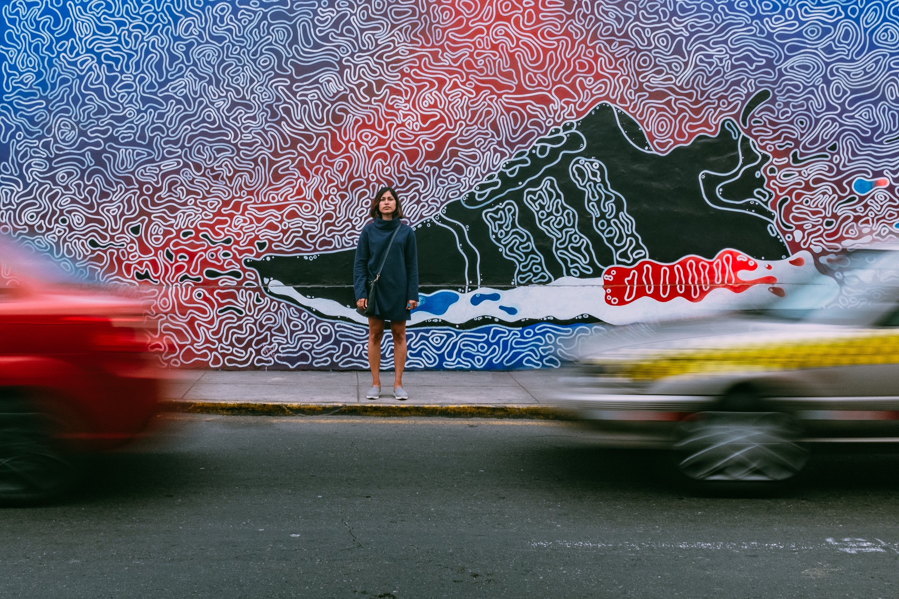 time lapse photography of woman wearing blue jacket standing on concrete pathway in front of two vehicles passing on concrete road during daytime
