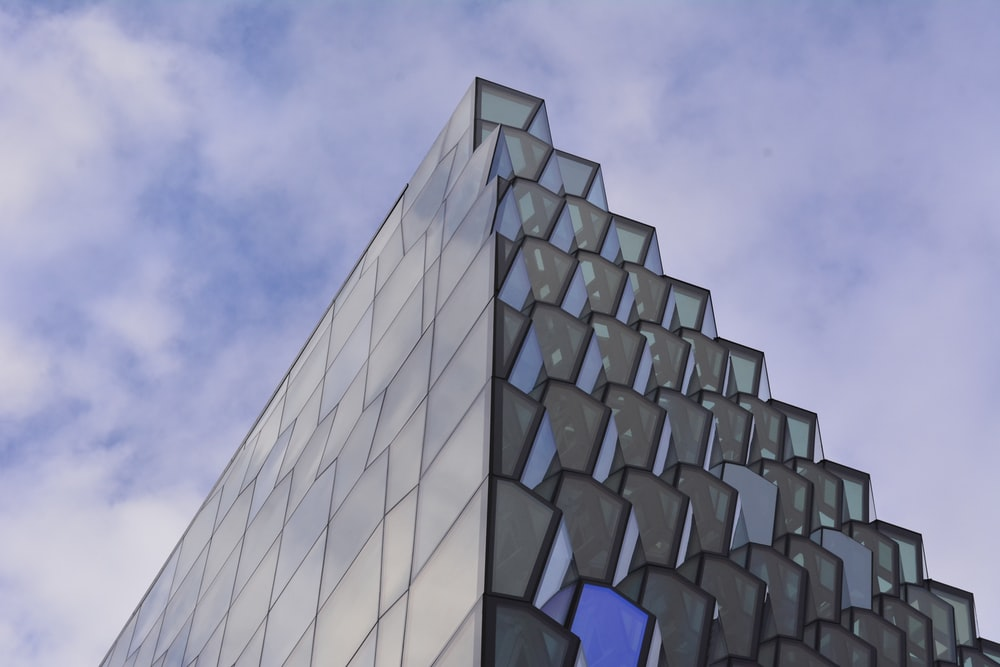 low angle photography of glass building under cloudy sky at daytime