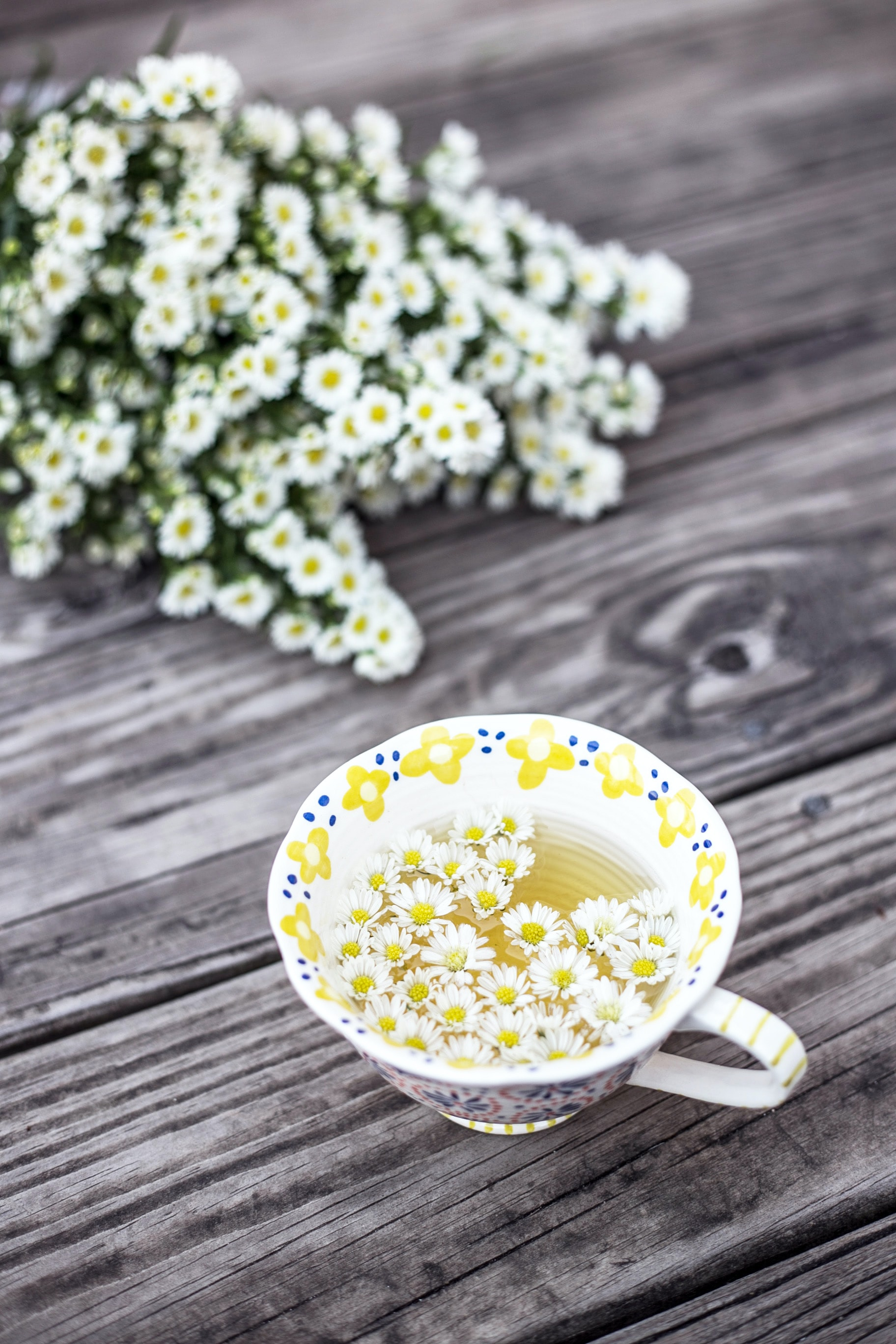 white and yellow cup with flowers on table