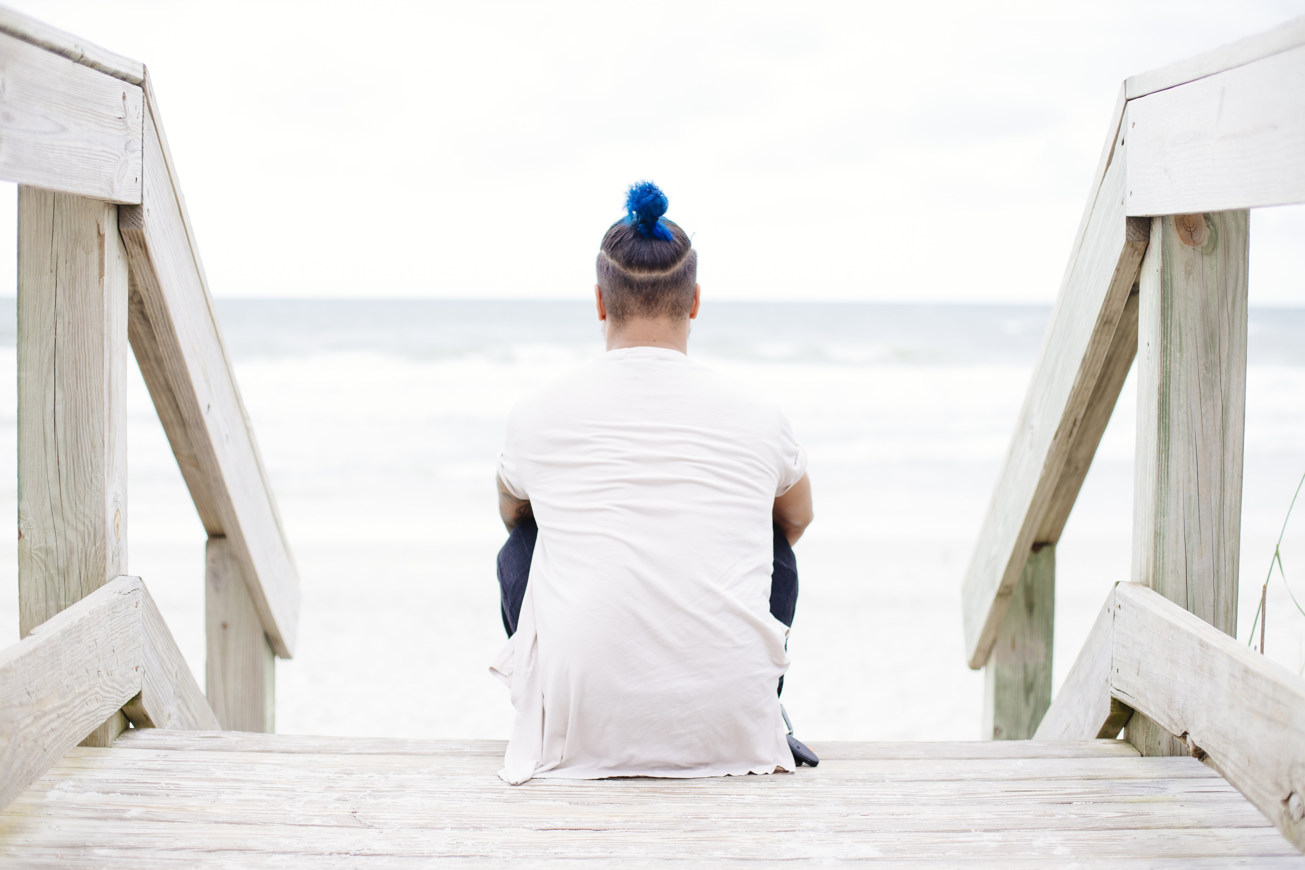A man with a blue-dyed bun sitting on wooden stairs near the sea