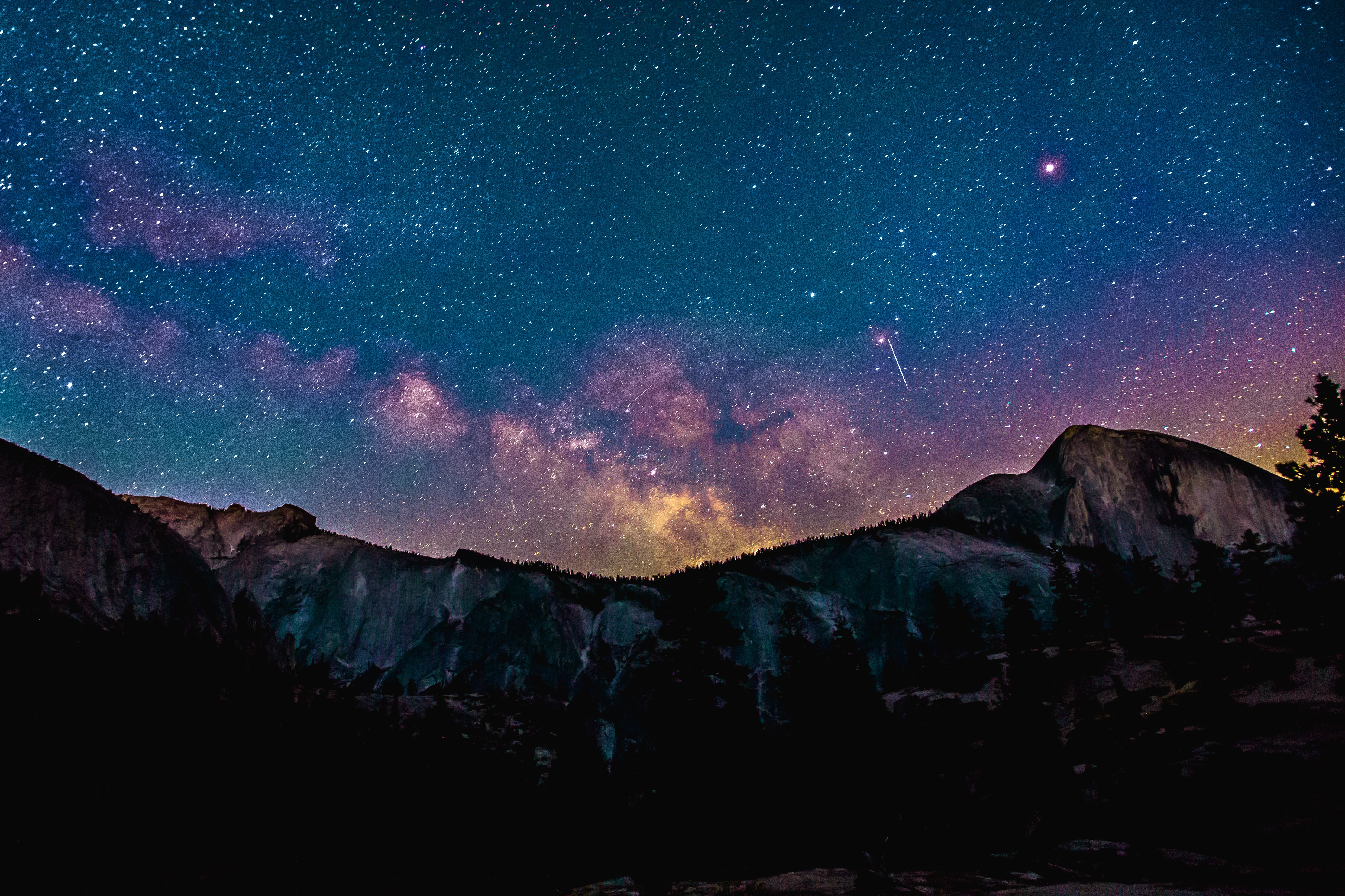 Purple-hued constellations in the night sky over a mountain ridge