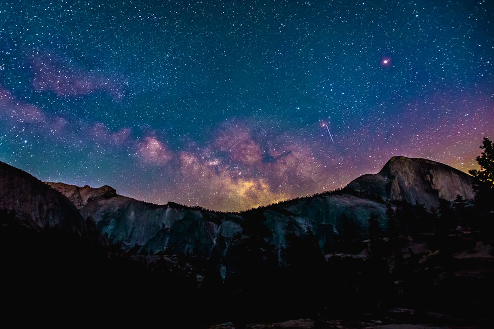 Purple Hued Constellations In The Night Sky Over A Mountain Ridge