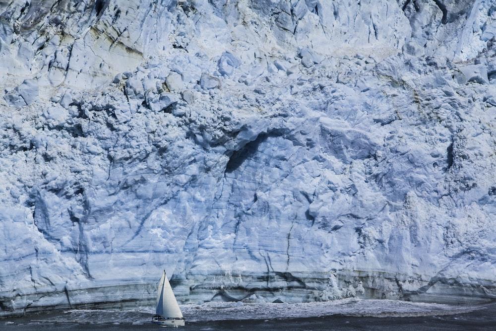 white sailboat near mountain