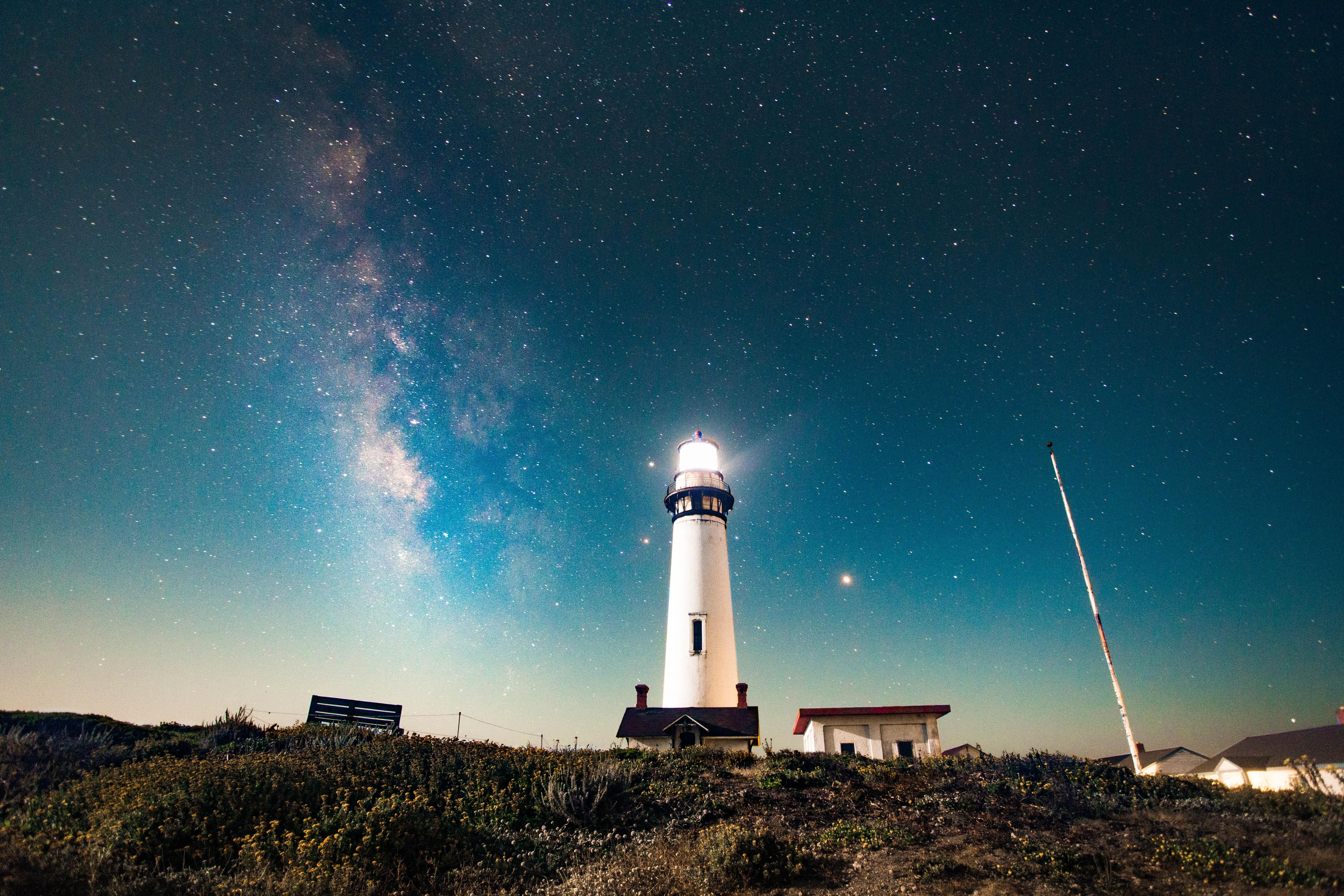photo of turned on white lighthouse