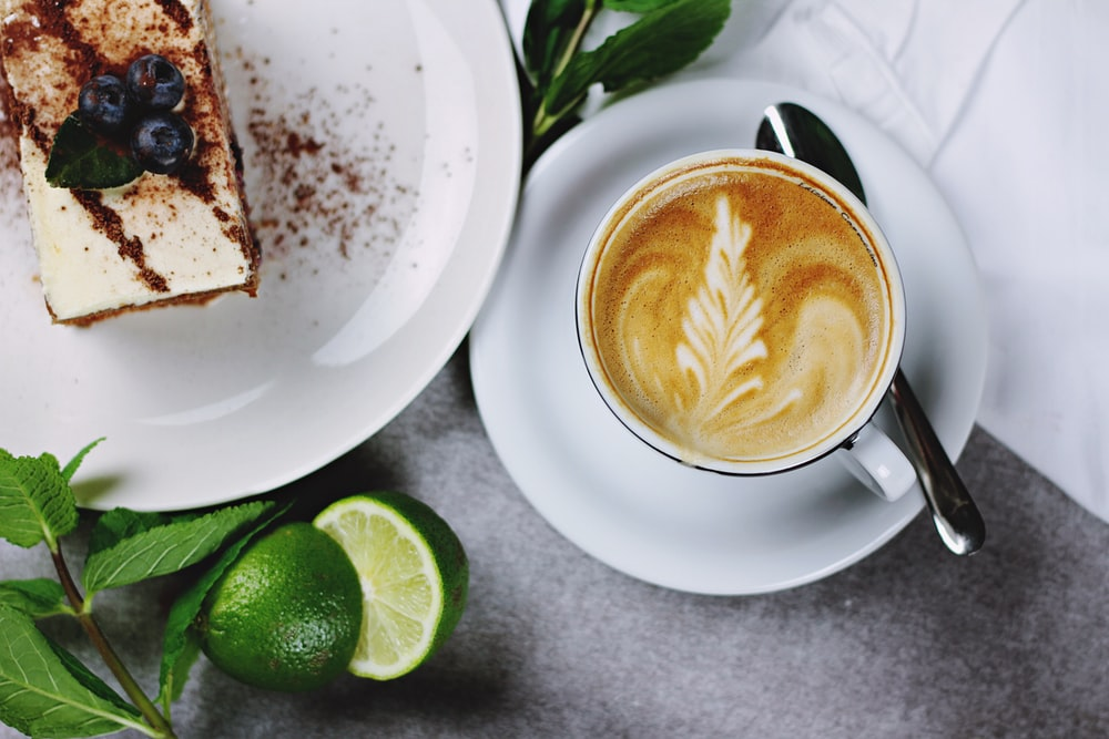 flat lay photography of coffee in teacup near plate of sliced cake