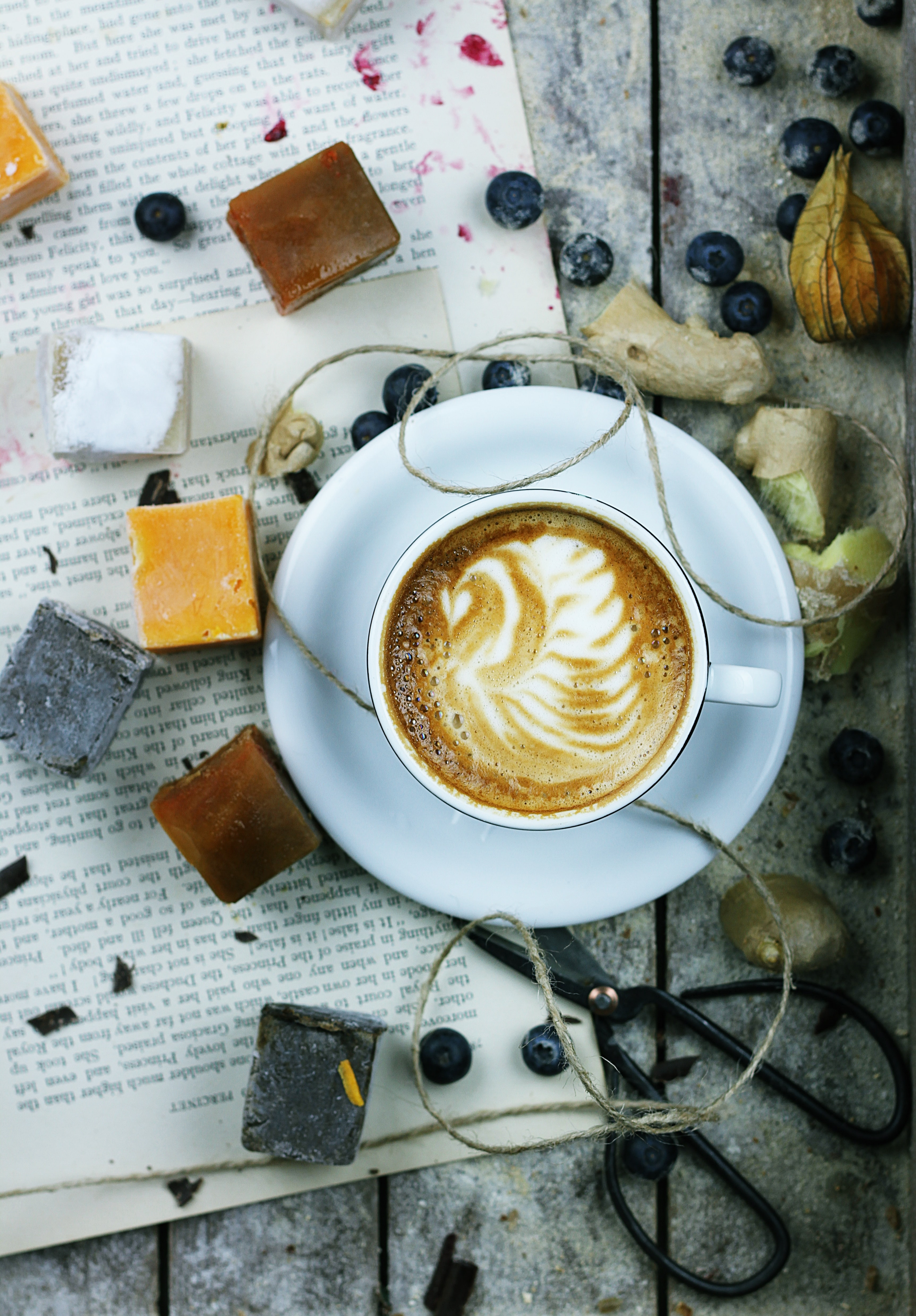 An overhead shot of a cup of coffee with latte art surrounded by blueberries and various trinkets