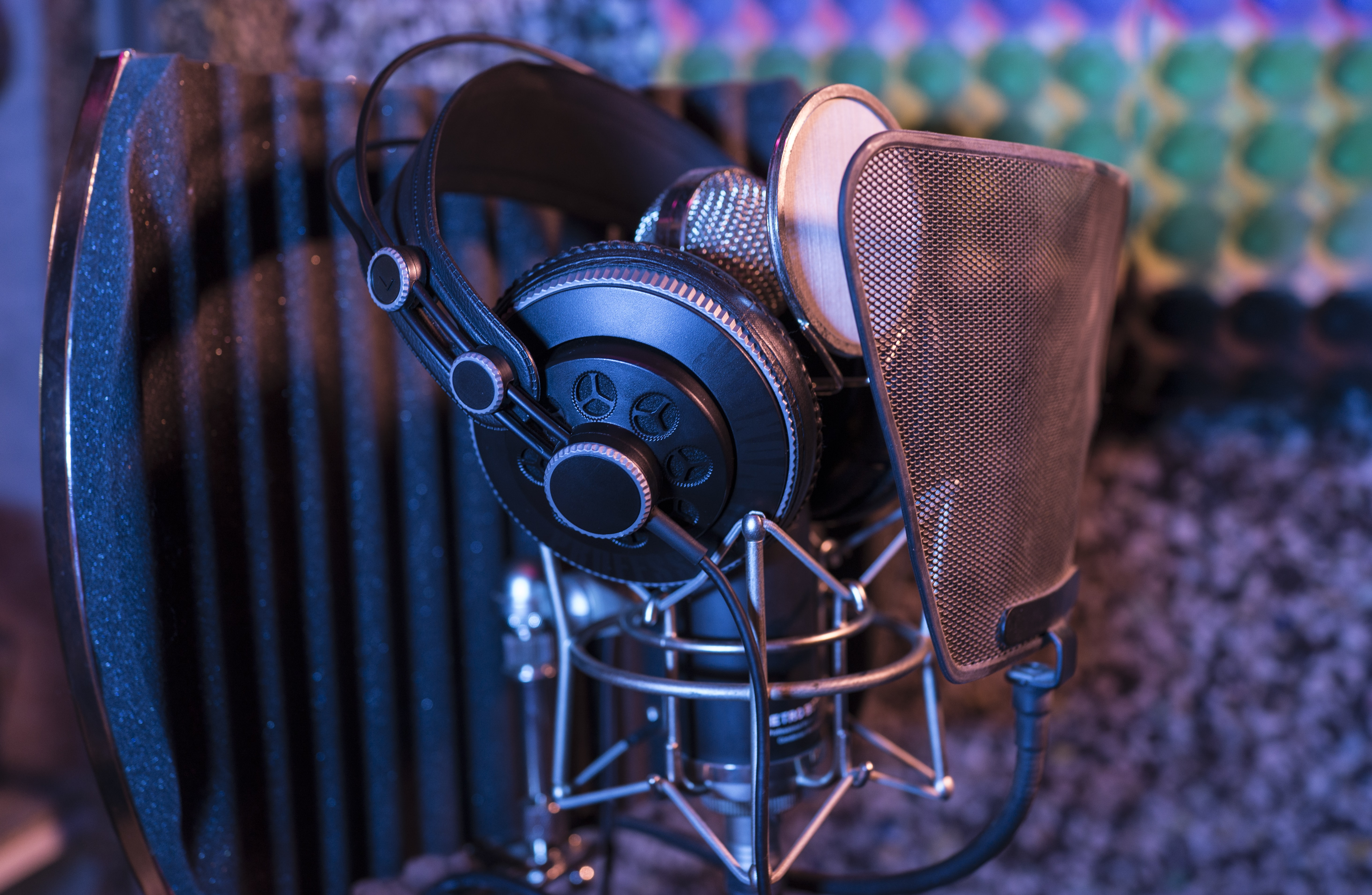 Professional studio headphones resting on a condenser microphone with a pop filter