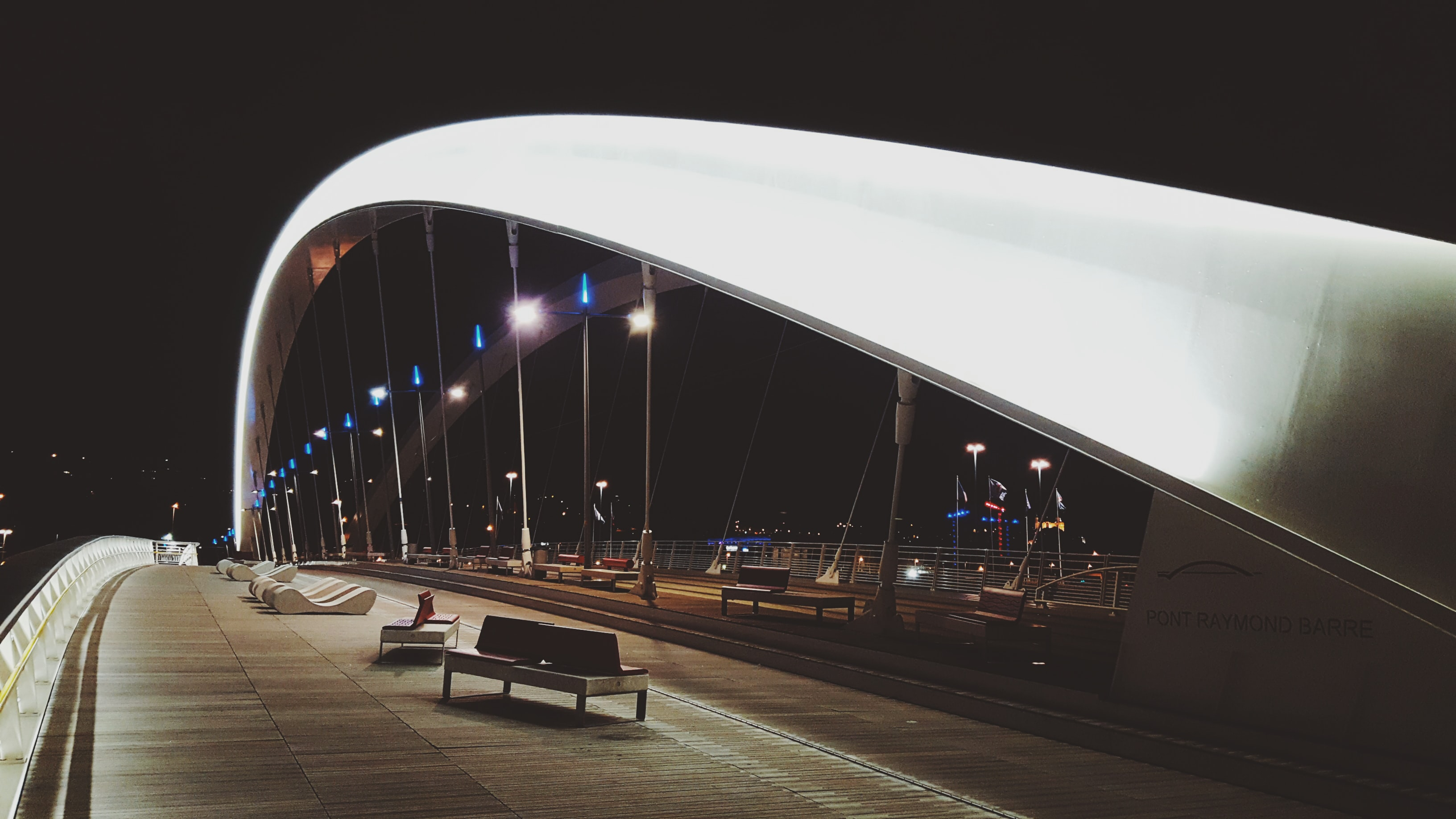 Pont Raymond-Barre at night with the arches and modern style benches along the bridge.