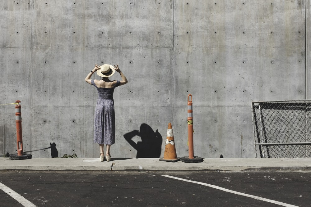 woman in gray dress facing a wall
