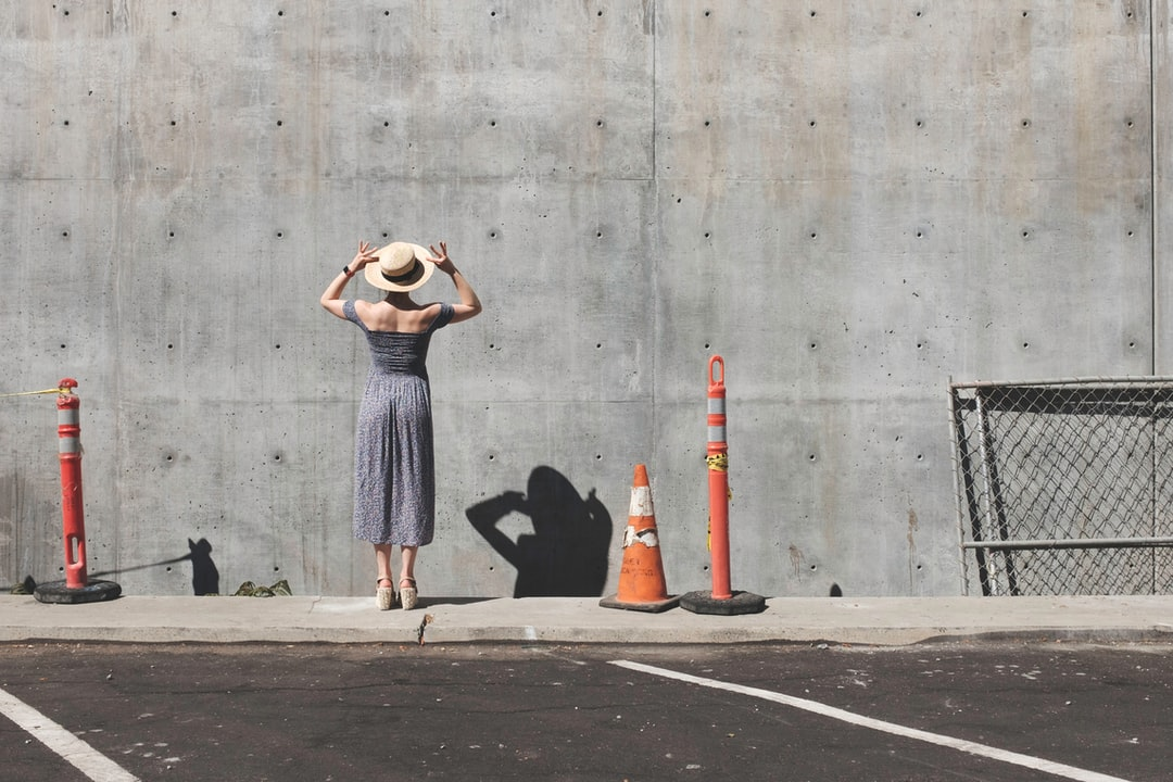 Woman in a dress by a wall