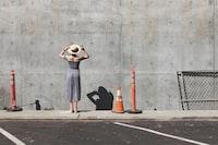 woman in gray dress facing a wall