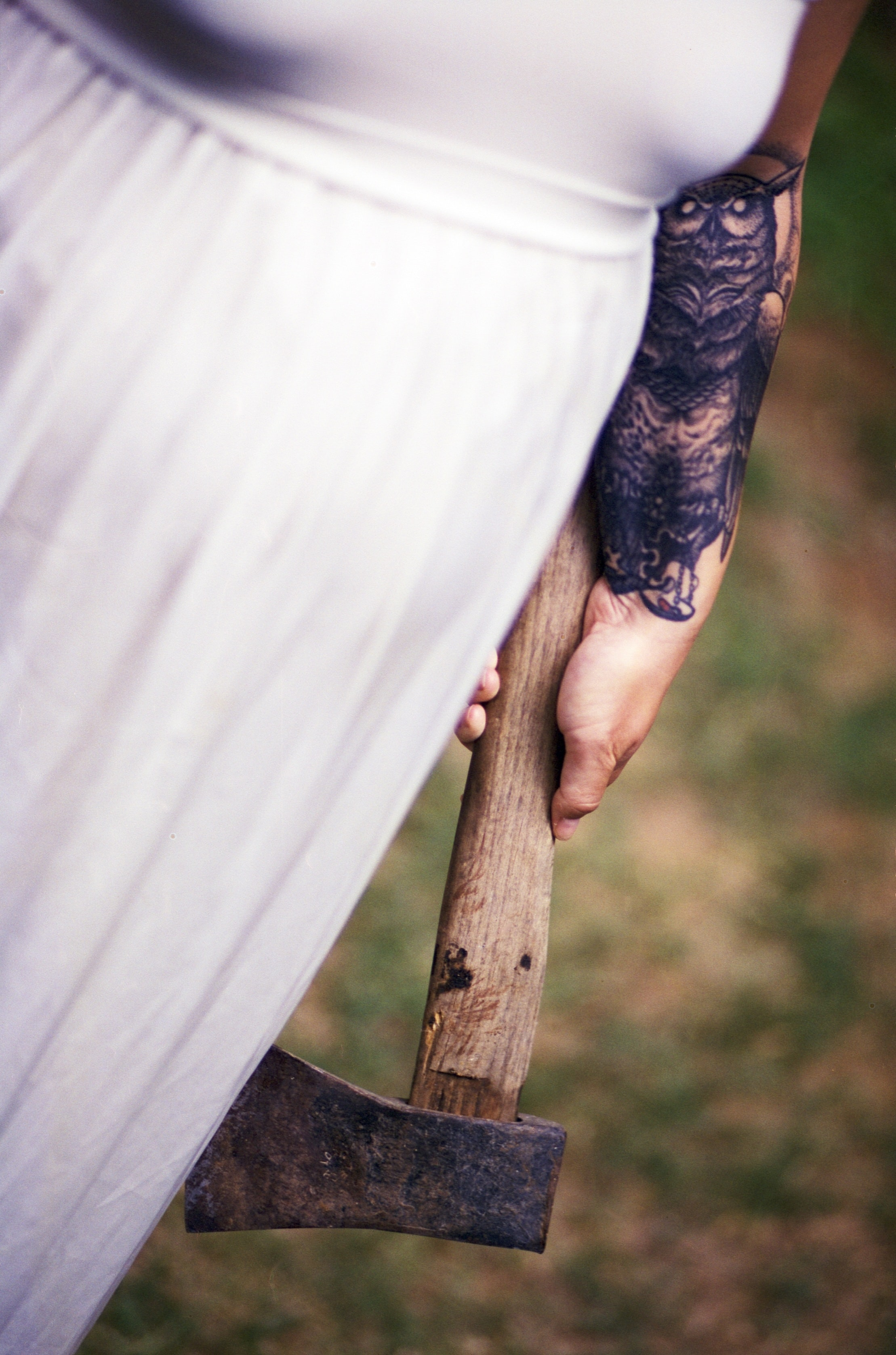 A lady in a white dress holding a rusty axe.