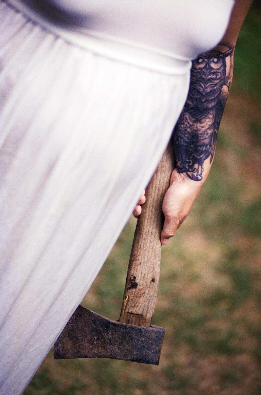 woman wearing white shirt holding axe
