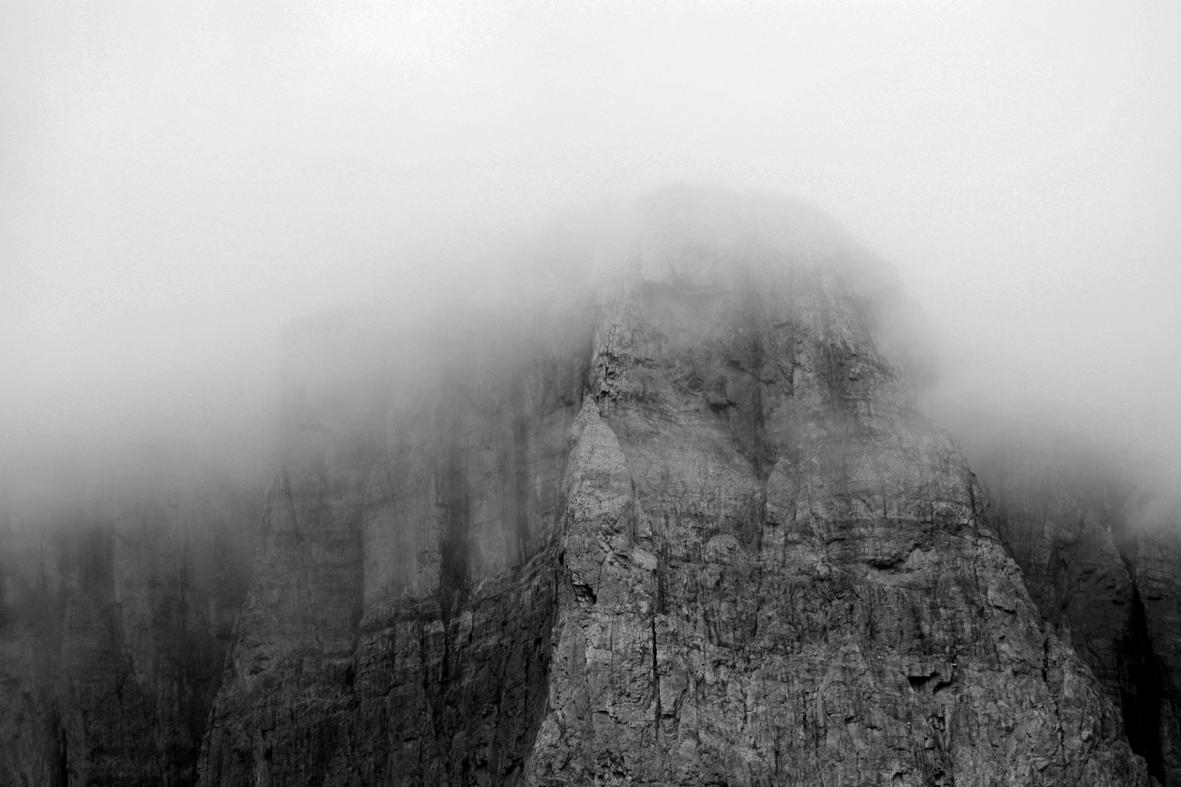 Gray rocky facade of Castle Mountain disappears into the fog