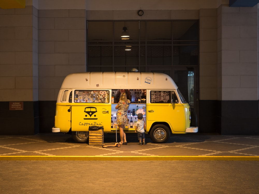 woman and child standing in front of yellow bus in car park