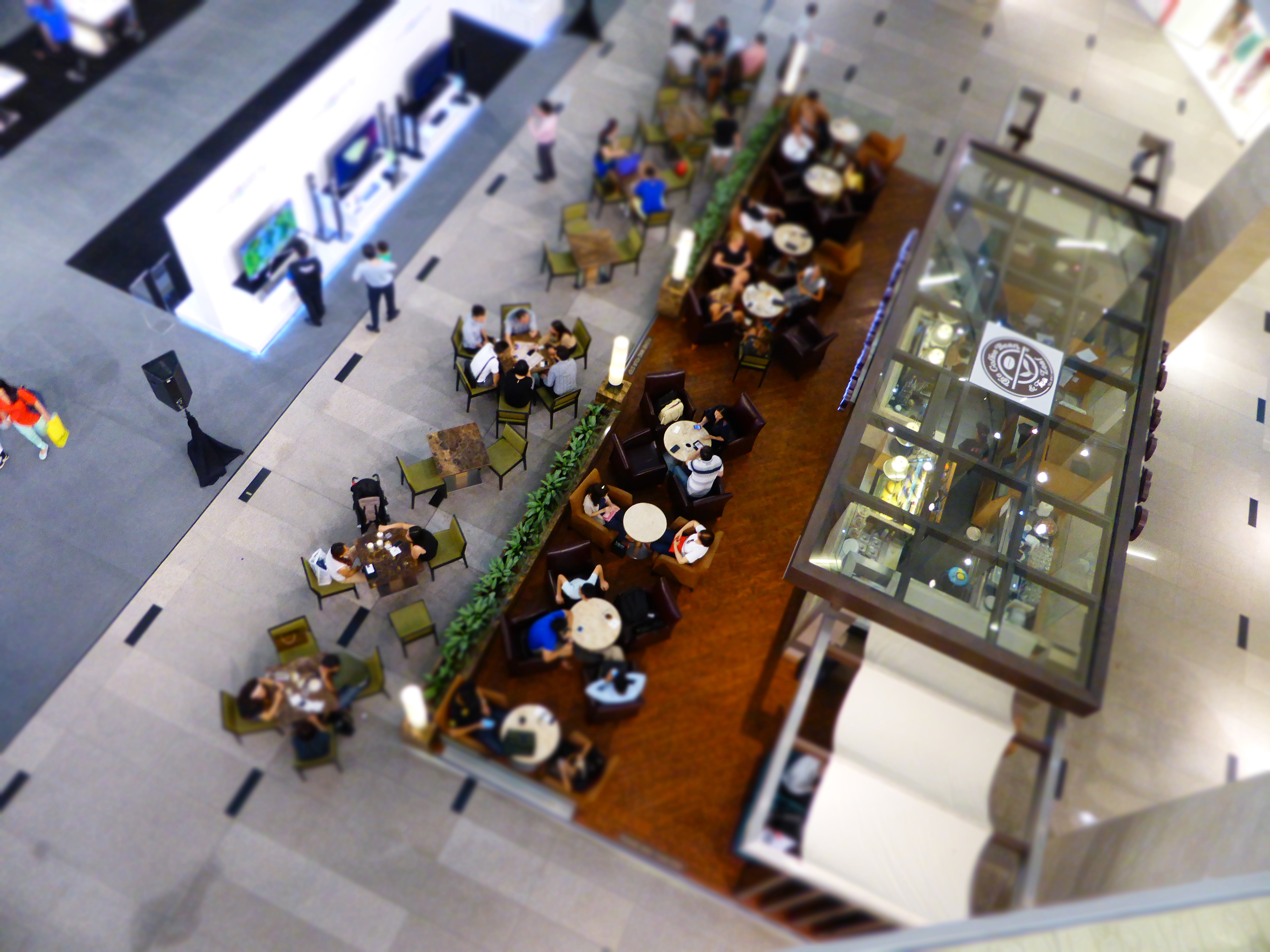 An overhead shot of people at a table in a shopping mall cafeteria