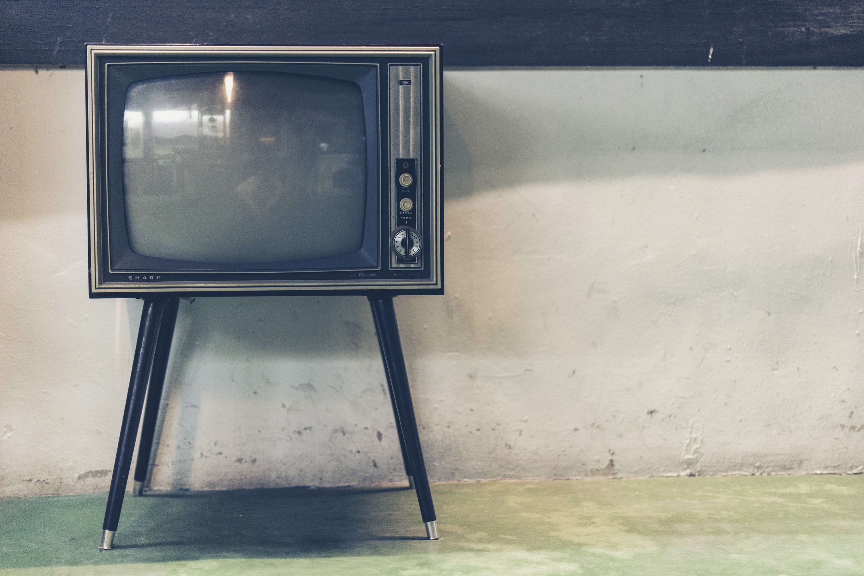 An old television set near a dilapidated wall