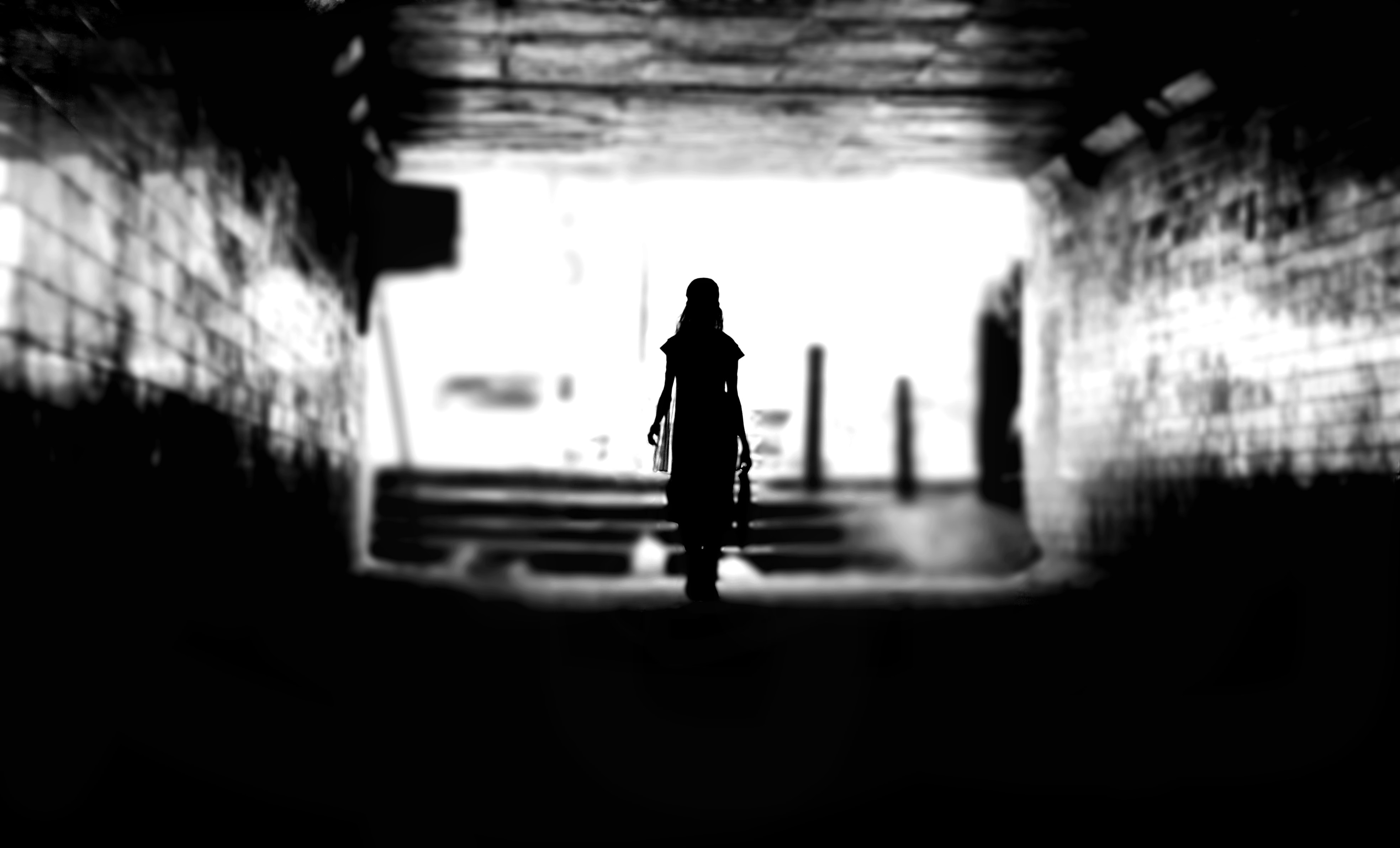 Black and white shot of lone woman silhouette walking through brick wall tunnel, Dadar
