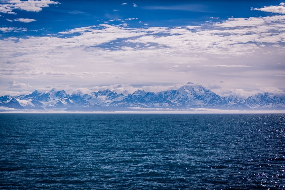landscape photography of snow covered mountain range across body of water