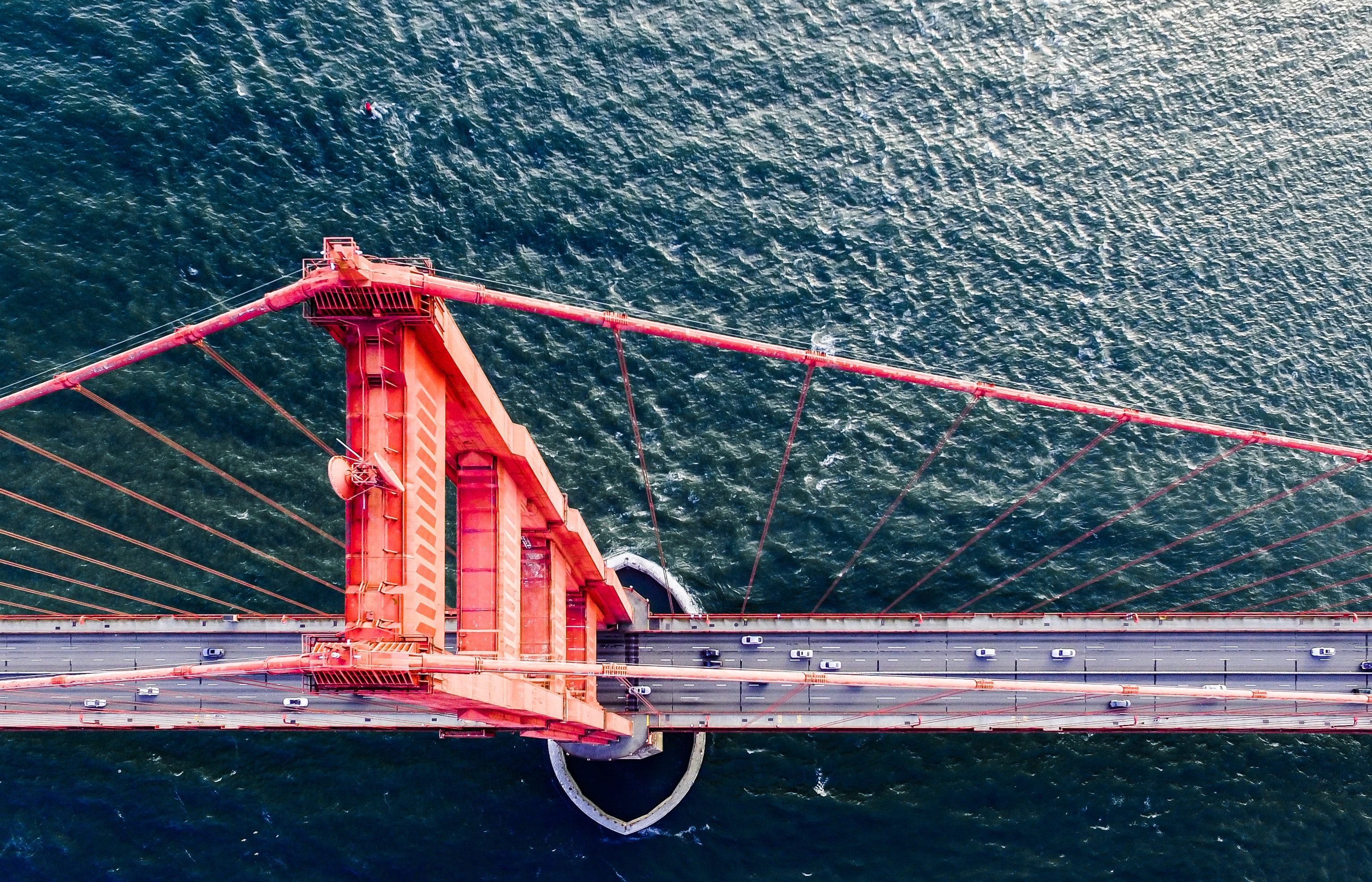 Drone view of cars driving along San Francisco Golden Gate Bridge and water