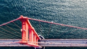 Looking down over one of the pillars of the Golden Gate Bridge to the roadside and water below