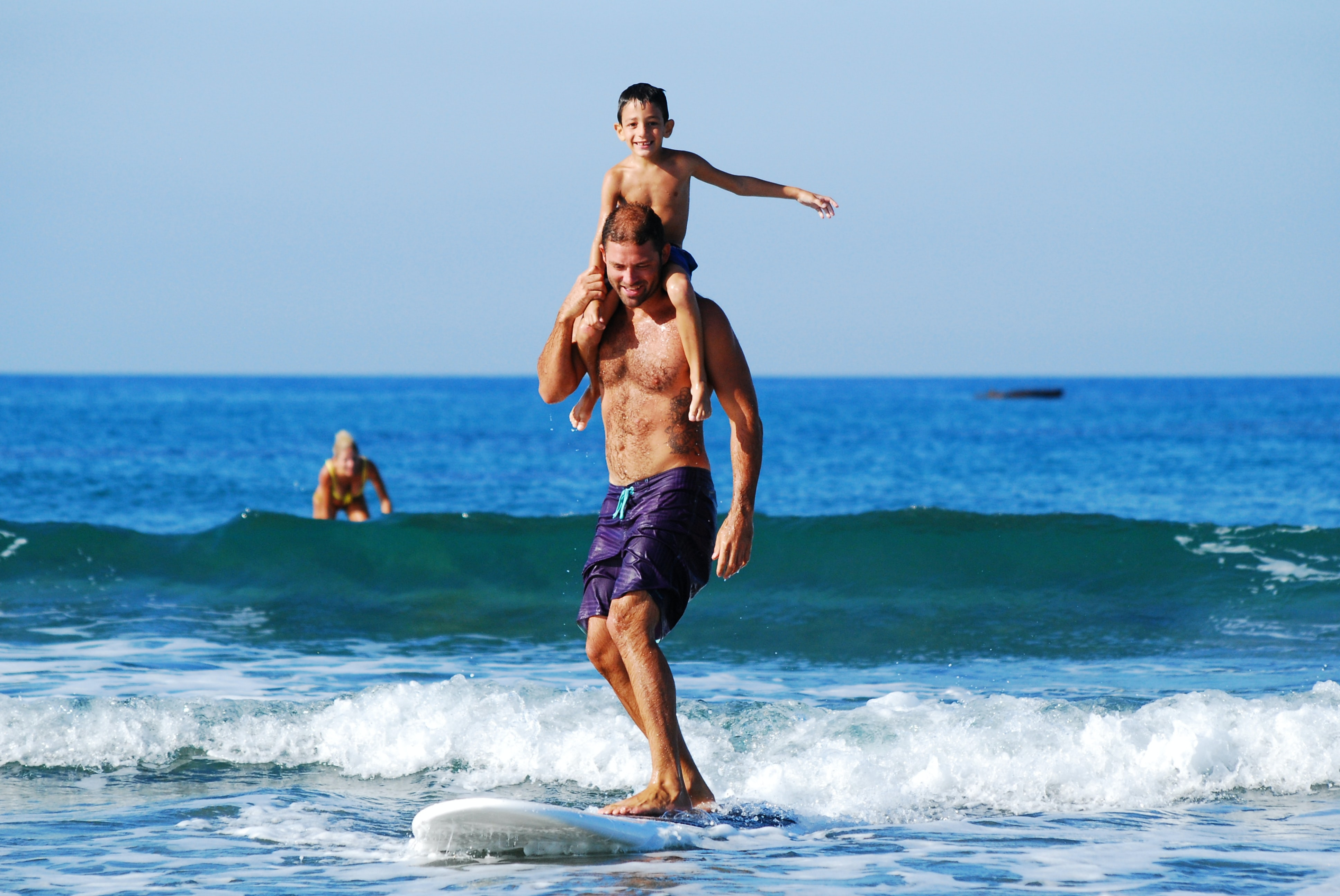 A man and his son surfing on a surfboard in the sea in Cyprus
