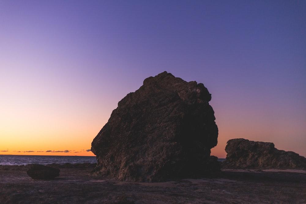 brown rock near sea shore