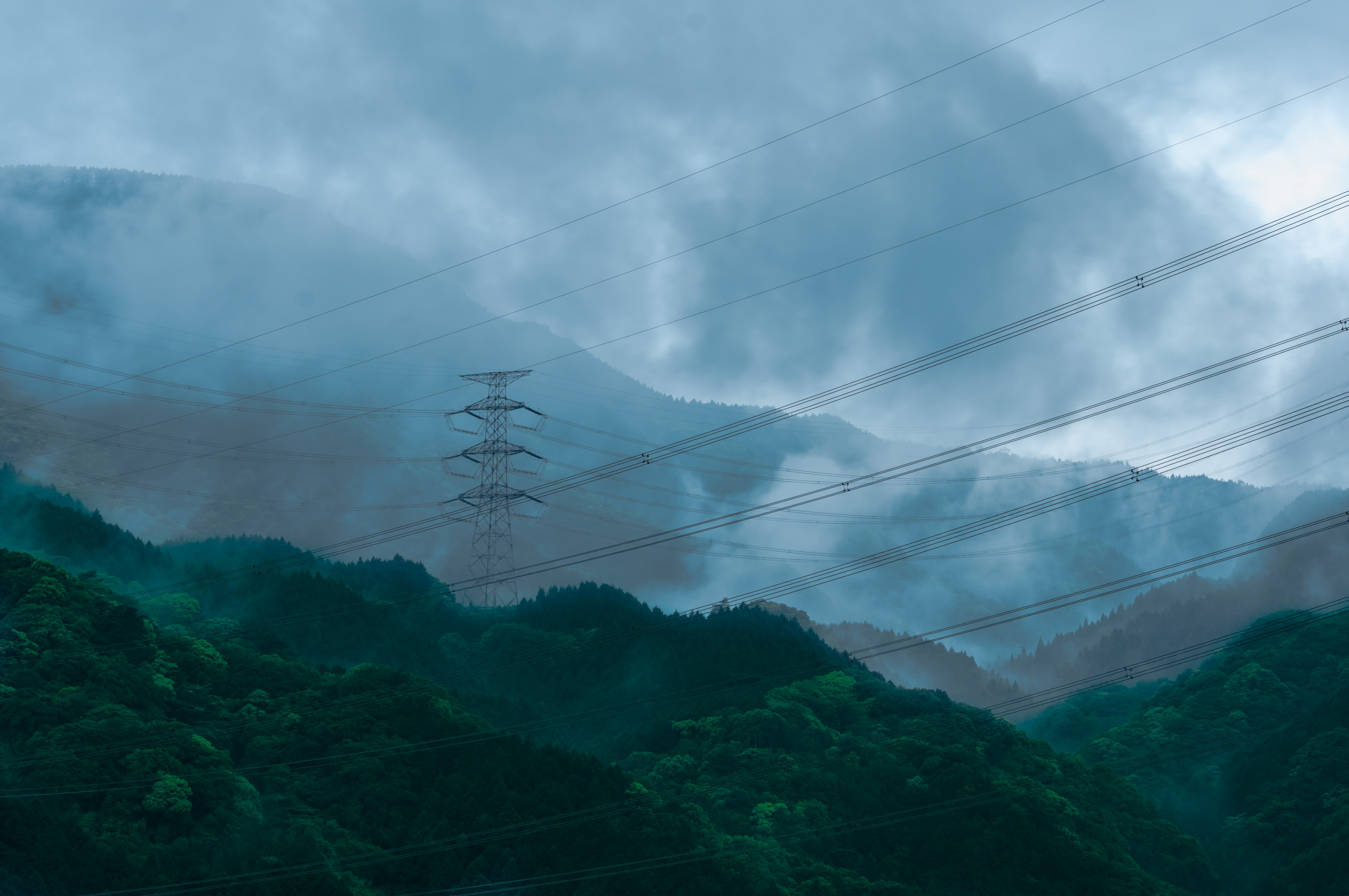 A number of power lines between transmission towers on wooded hills