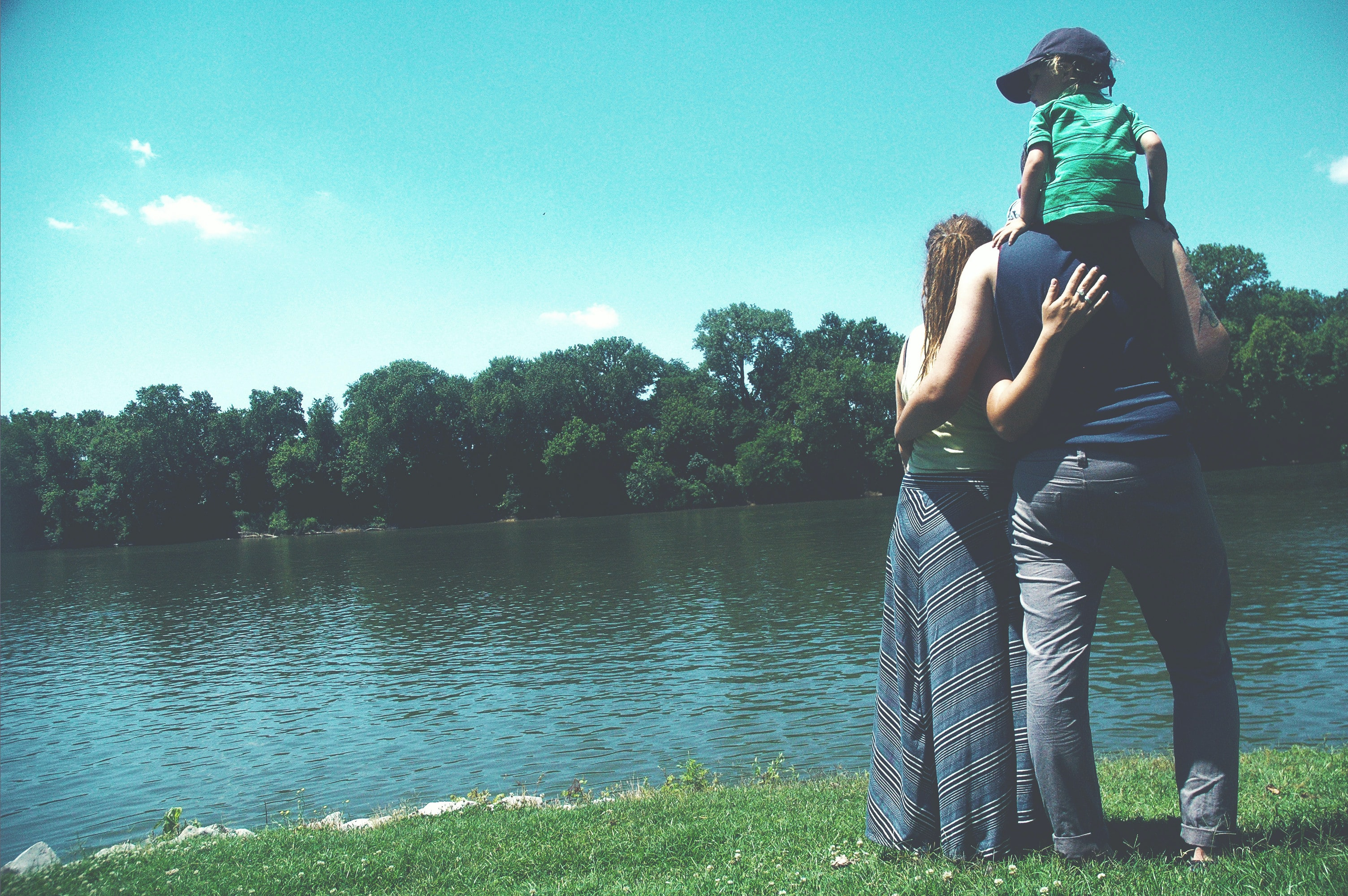 father, mother, and son standing on grass lawn near at body of water during daytime