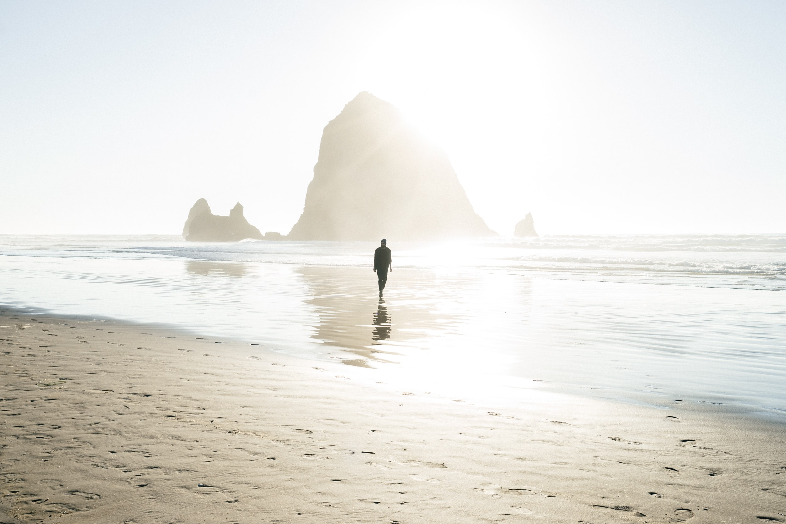 A silhouette of a man walking through the shallow water on a sandy beach