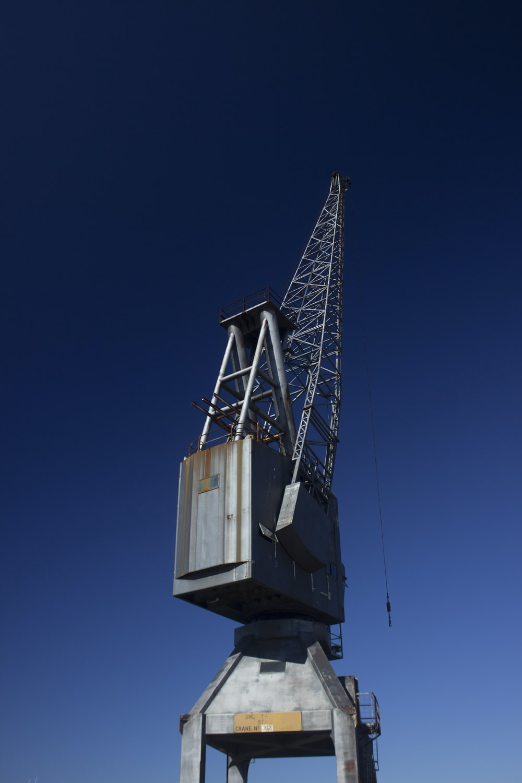 gray metal crane equipment under blue sky