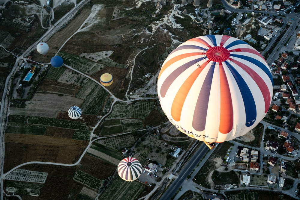 white and blue hot air balloon floating on city