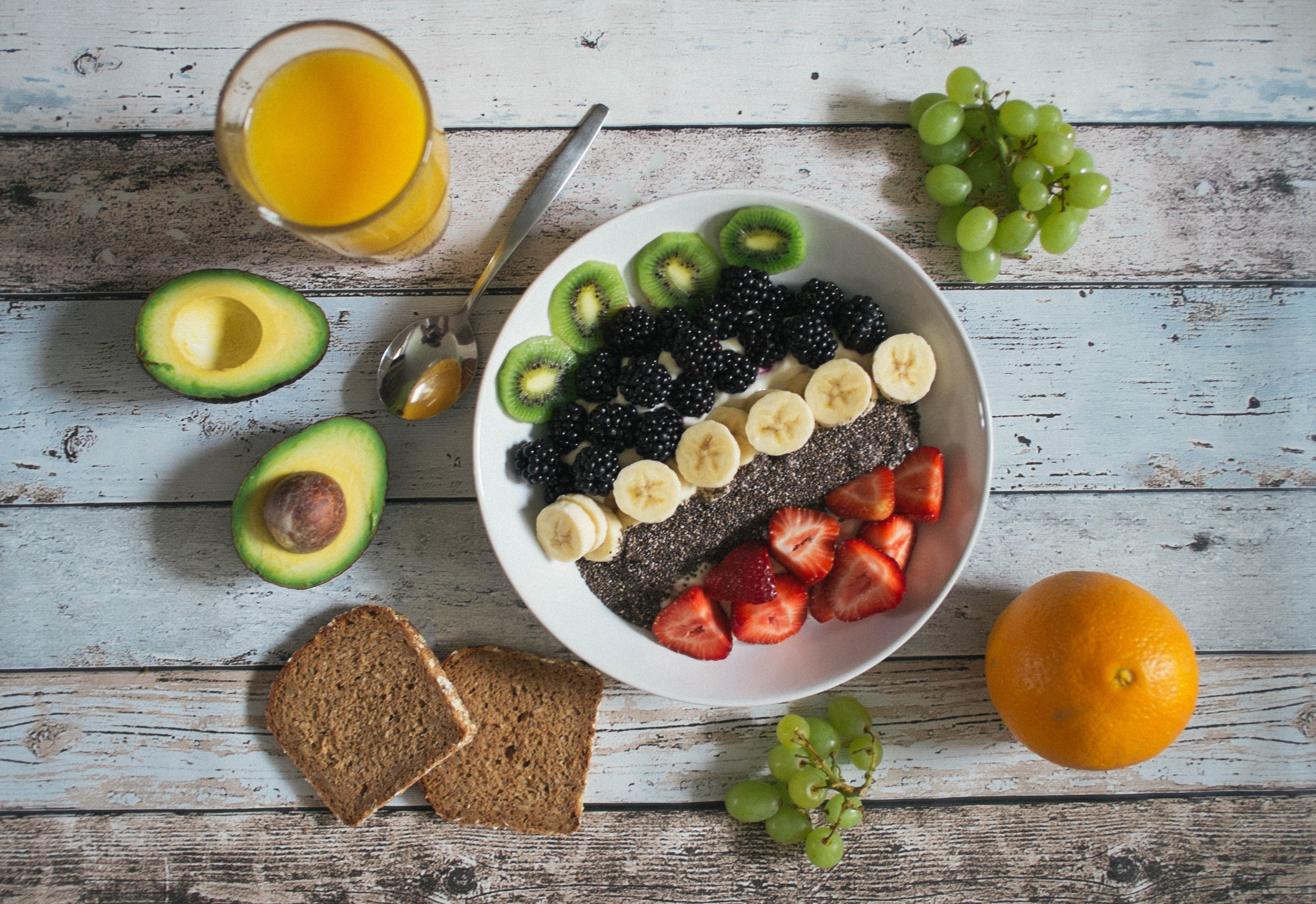 Trendy smoothie bowl with fresh fruit, avocado, chia seeds, and berries