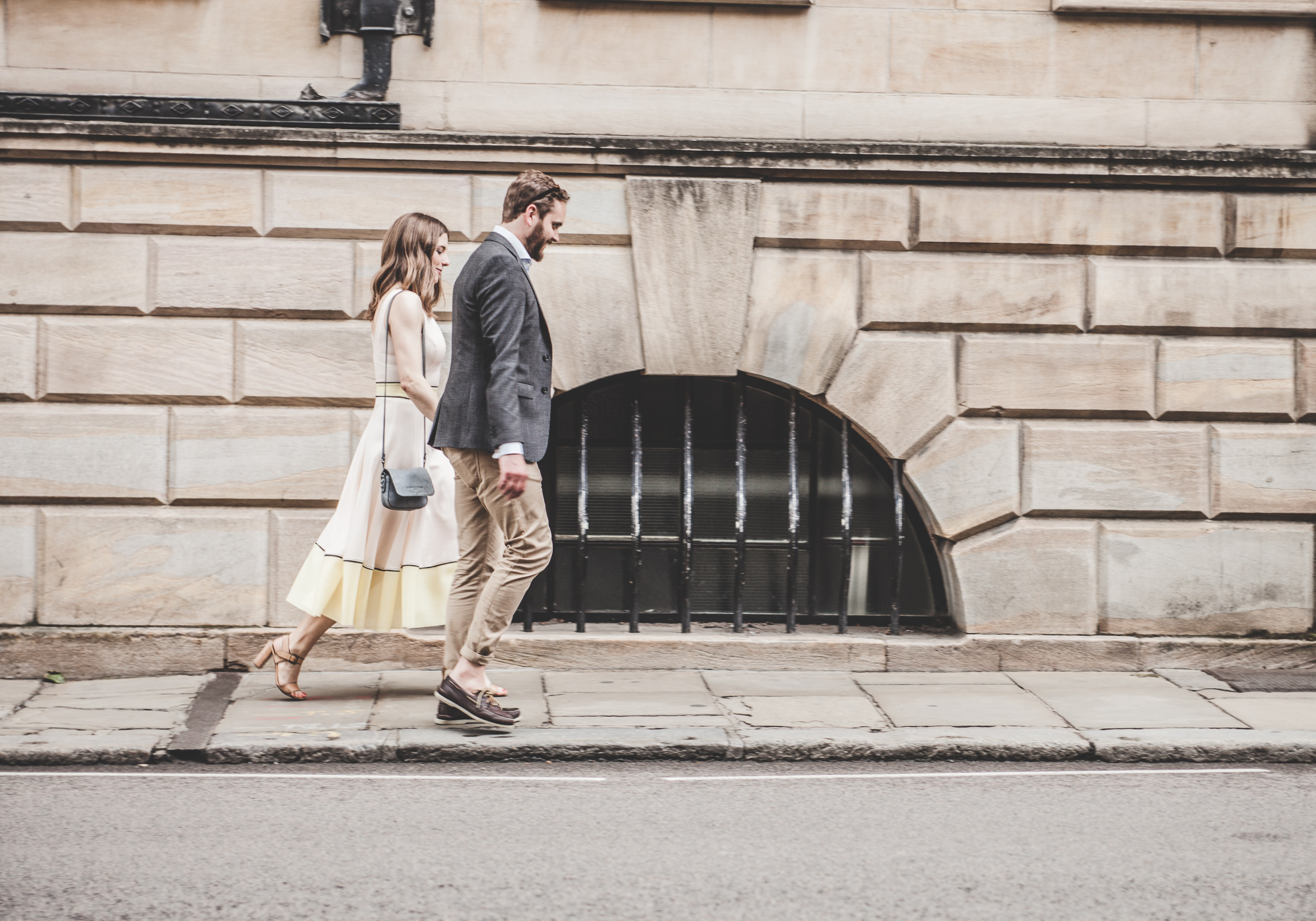 man and woman walking beside a road during daytime