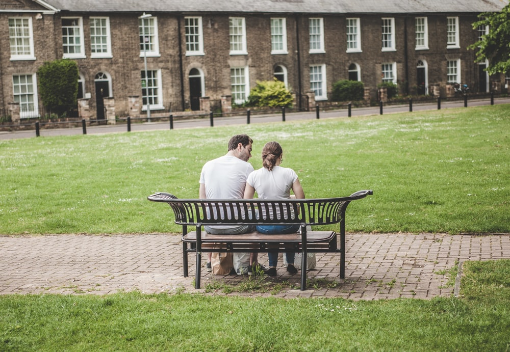 man and woman sitting on bench