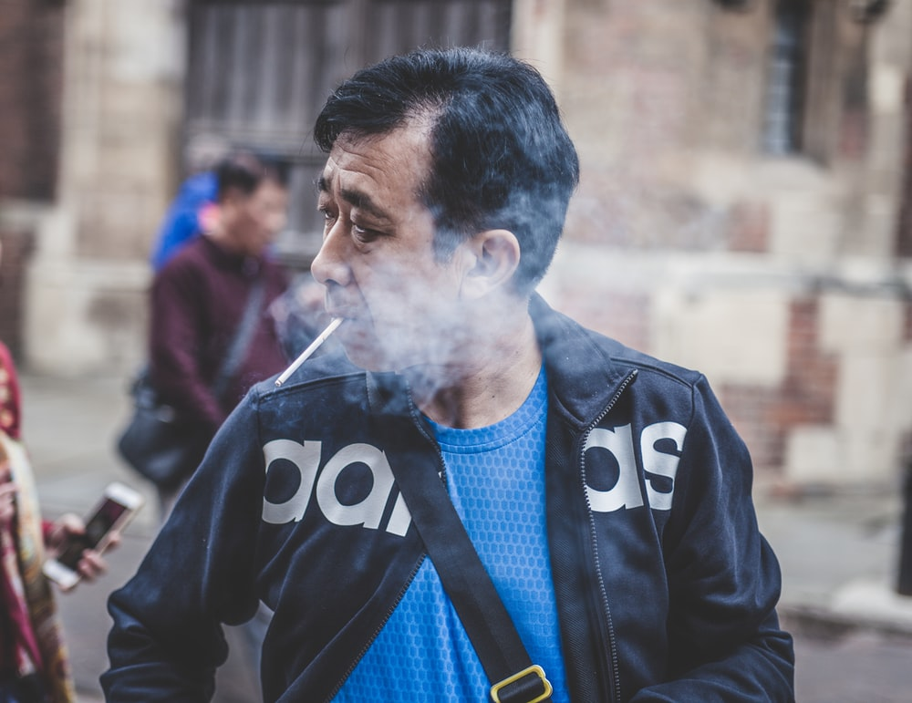man in black Adidas leather jacket smoking cigarette