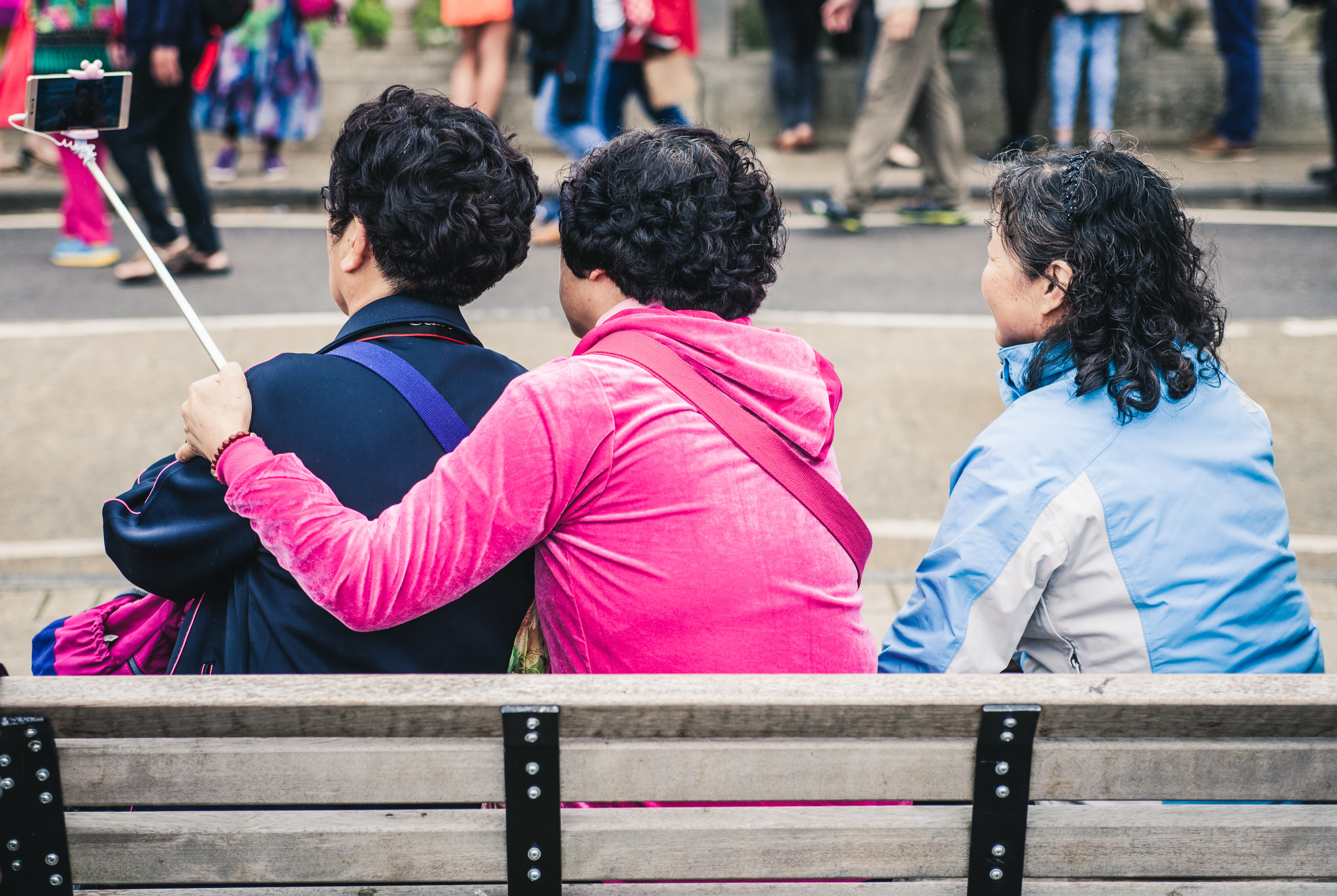 three person taking selfie while sitting on a bench during day time