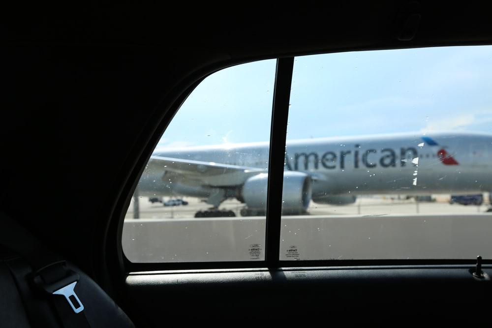 Silver American Airlines plane from taxi window in Miami with blue sky