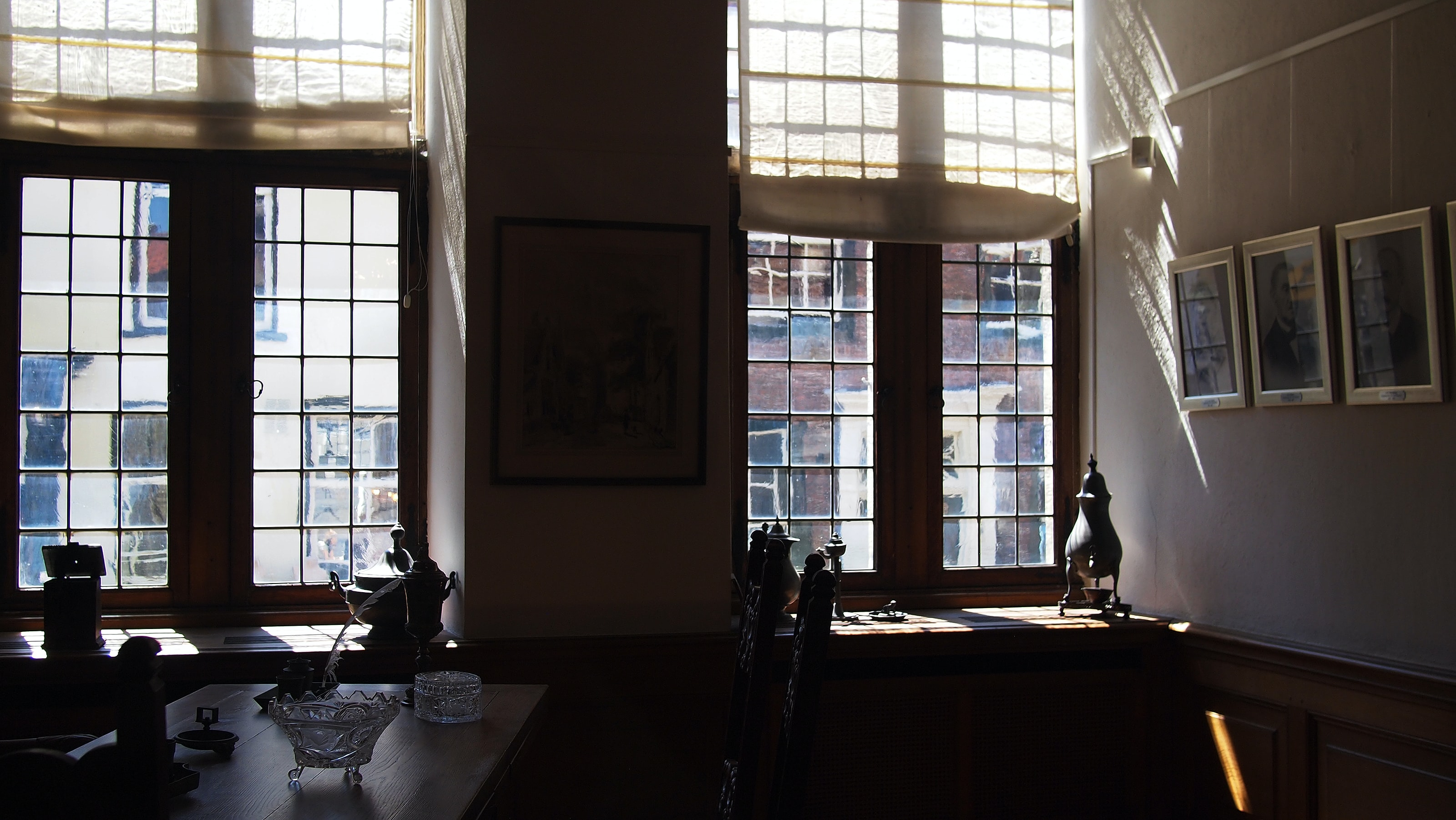 Interior of a house with pictures on the walls, tables, and windows facing an urban setting