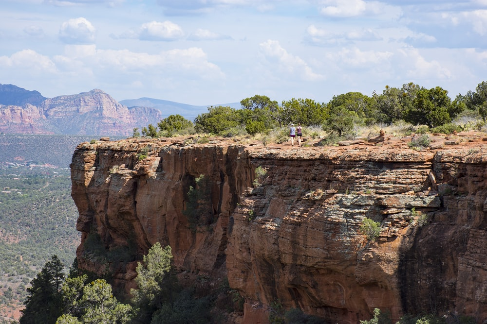 two person walks on brown cliff under clear blue sky during daytime